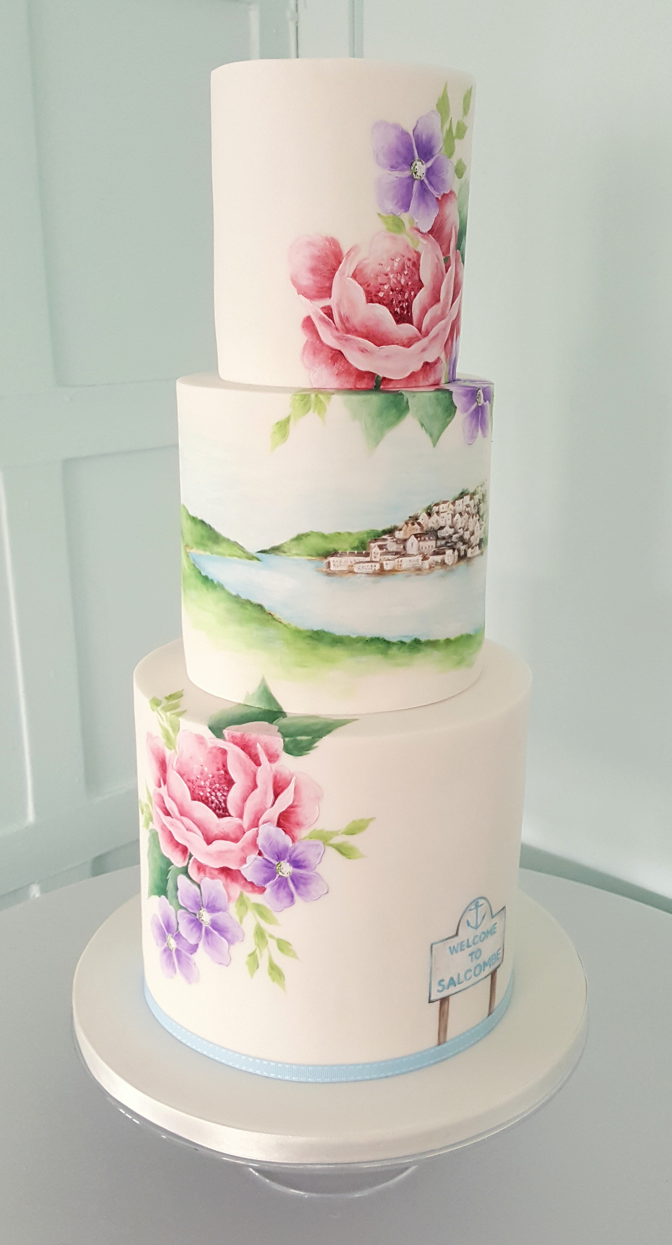 SALCOMBE HARBOUR  A hand painted landscape view of Salcombe harbour is a main focal point of this wedding cake design, surrounded by my signature blooms in shades to match the wedding decor. Landscapes of favorite places are a lovely way to add a personal touch to your cake!