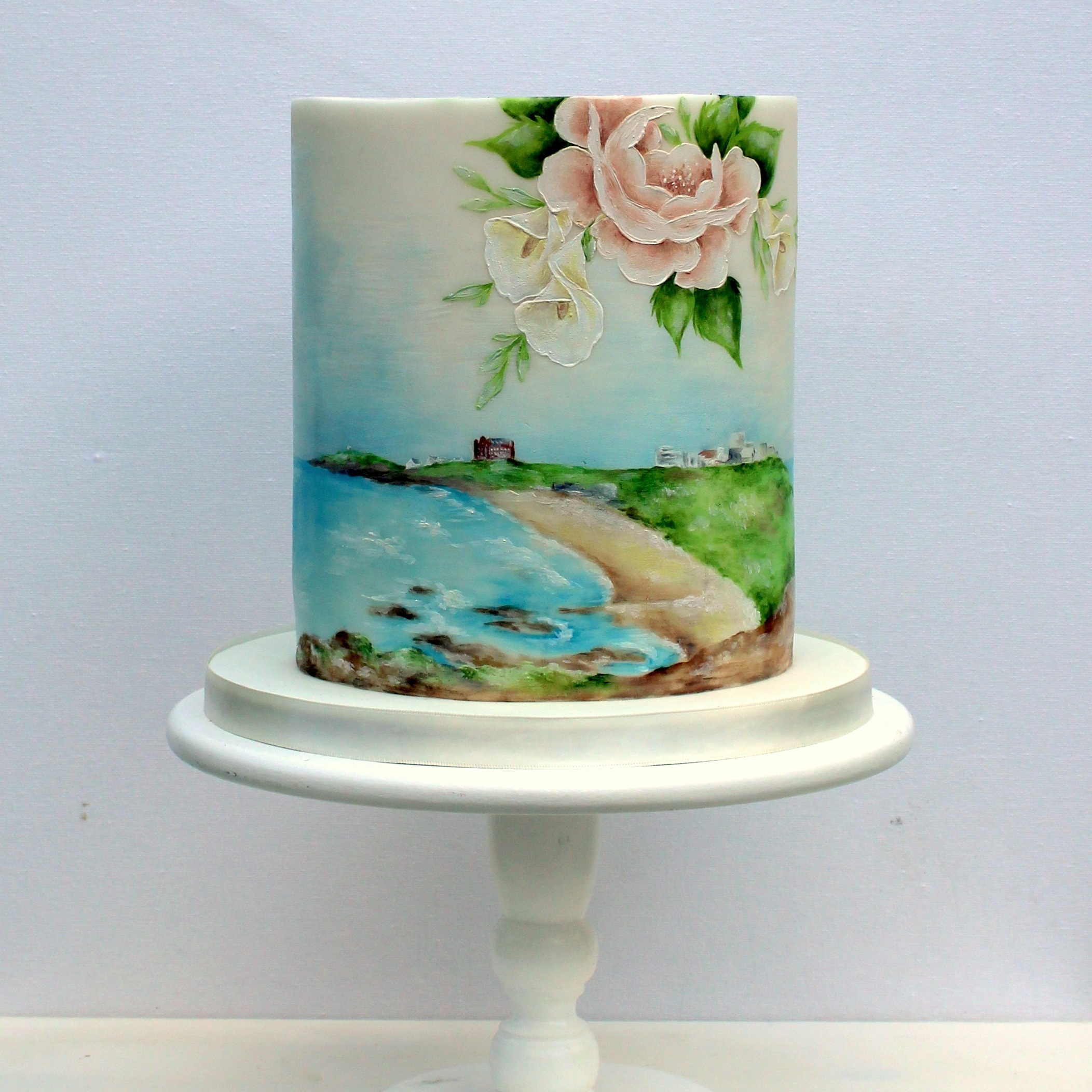 hand painted single tier wedding cake with landscape of fistral beach and calla lilys