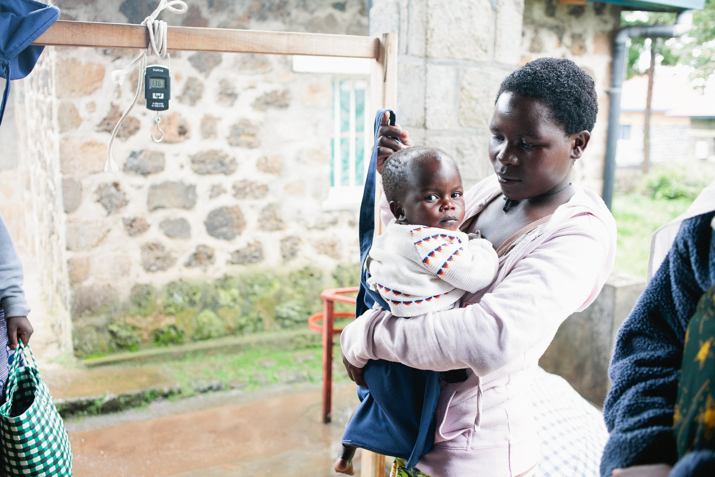 A caregiver helps weigh her child