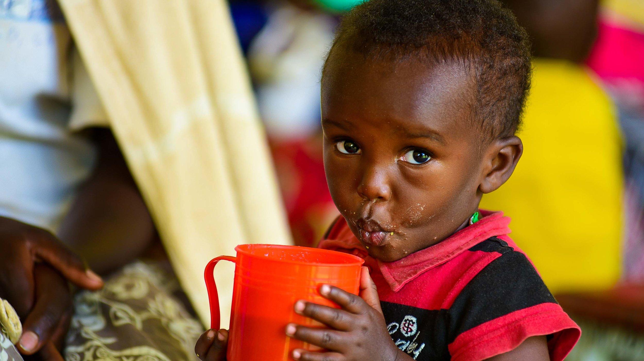 A child drinks Sosoma at a GHI health center training on family planning at the Gataraga Health Center in Musanze, Rwanda.
