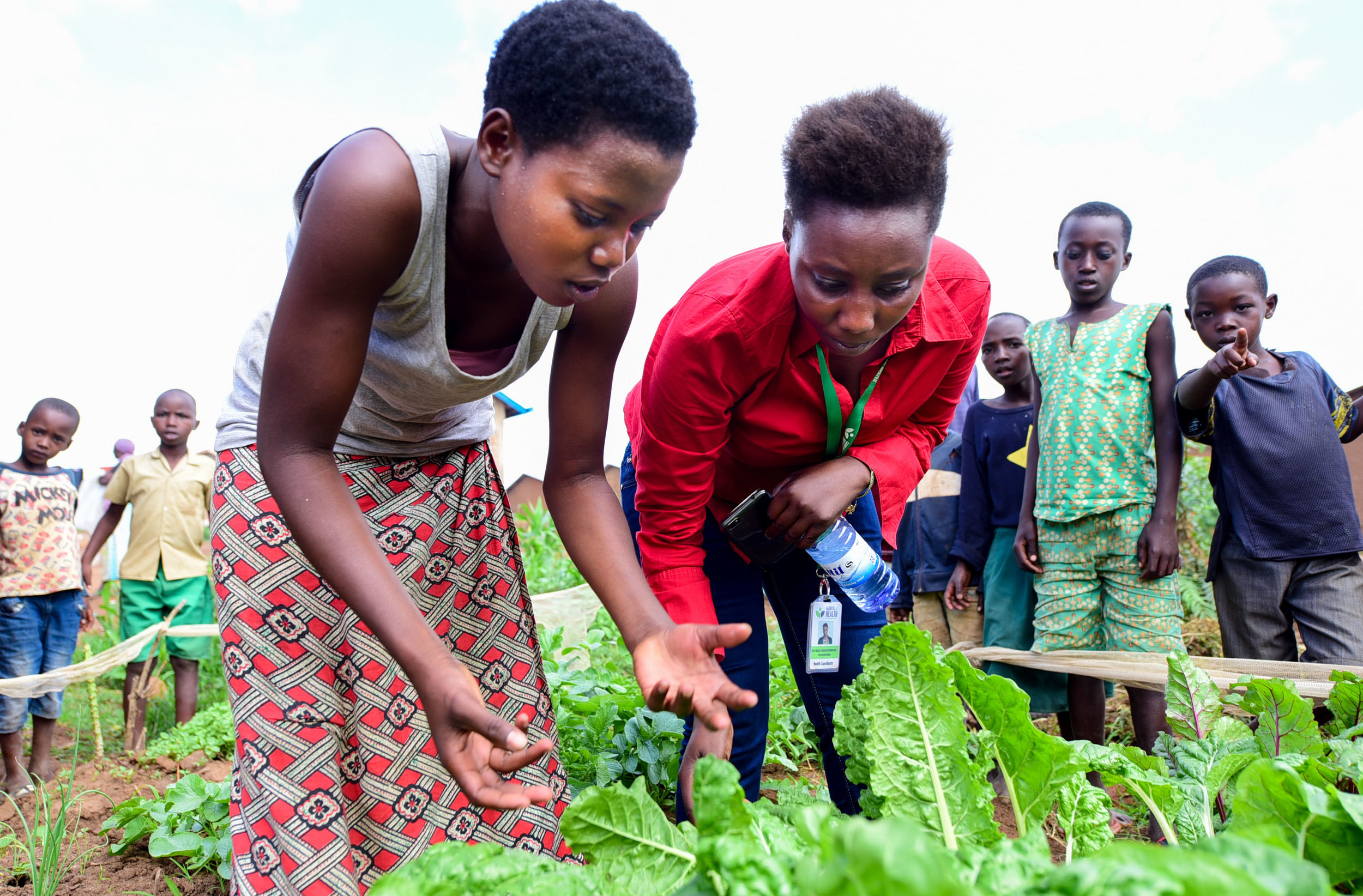 GHI Health Coordinator Annonciathe Niyibizi checks on the home gardens of GHI graduates in Mahama refugee camp.