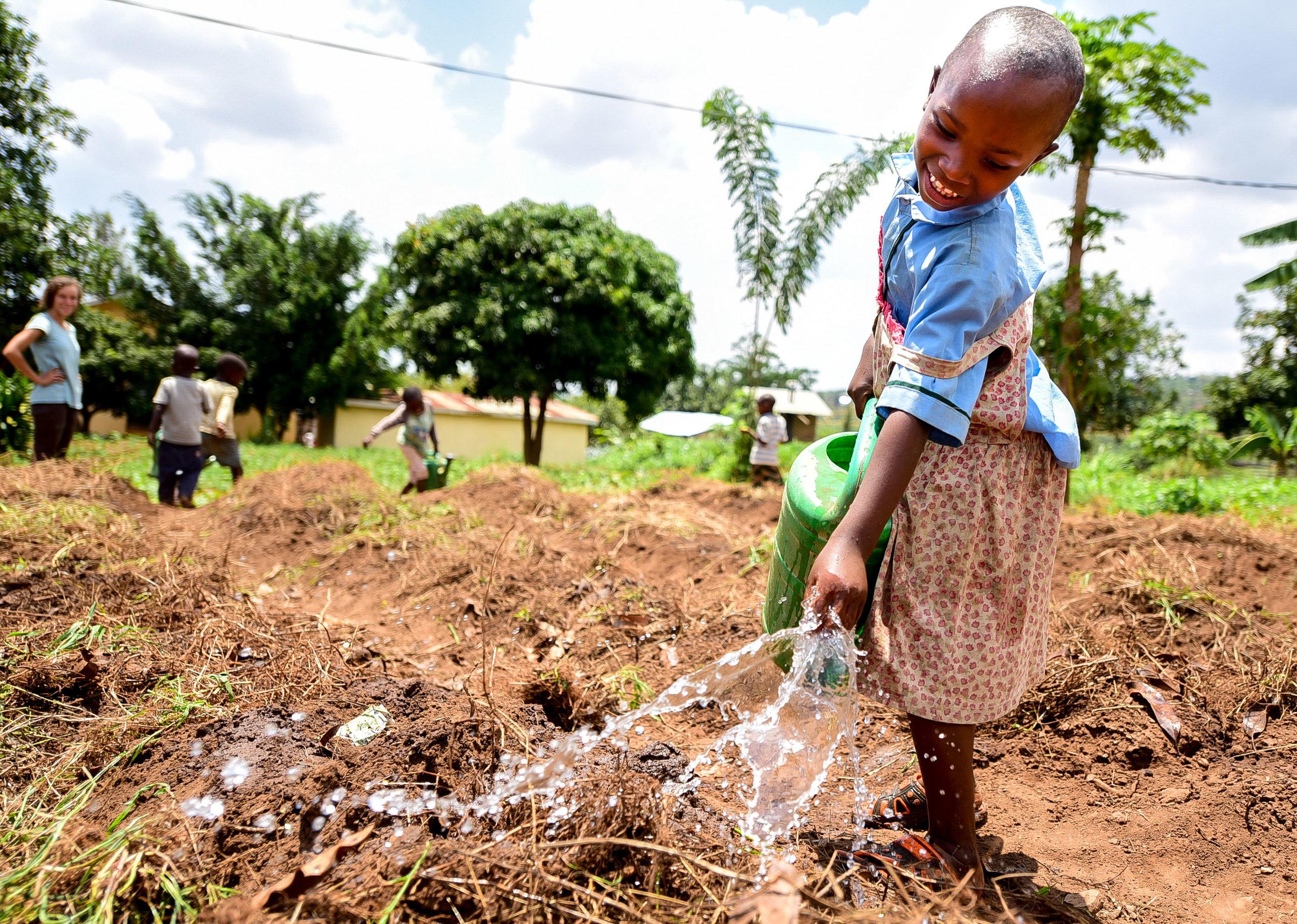 Iradukunda Florance, a member of GHI's Early Childhood Development program, helps water crops.