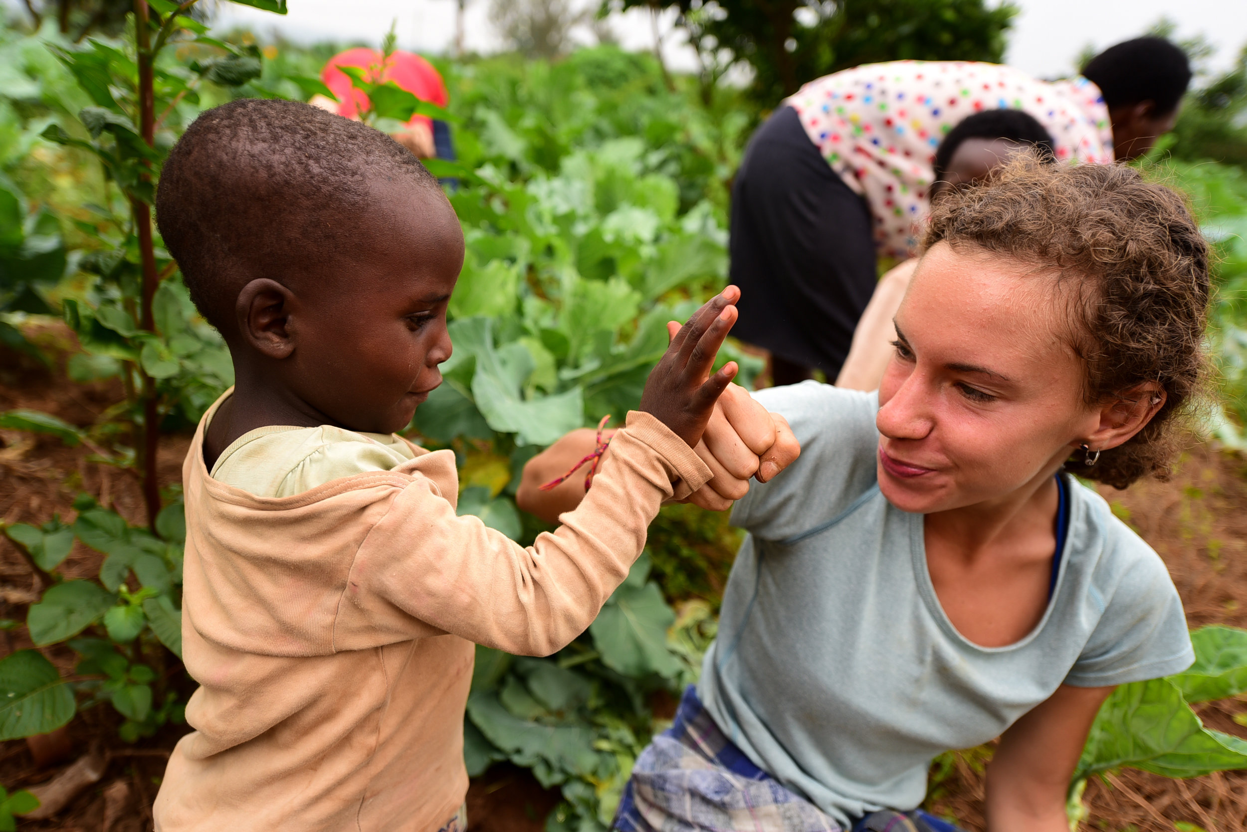 Jessie plays with Phiona at a GHI Umuganda Day in January, 2018.