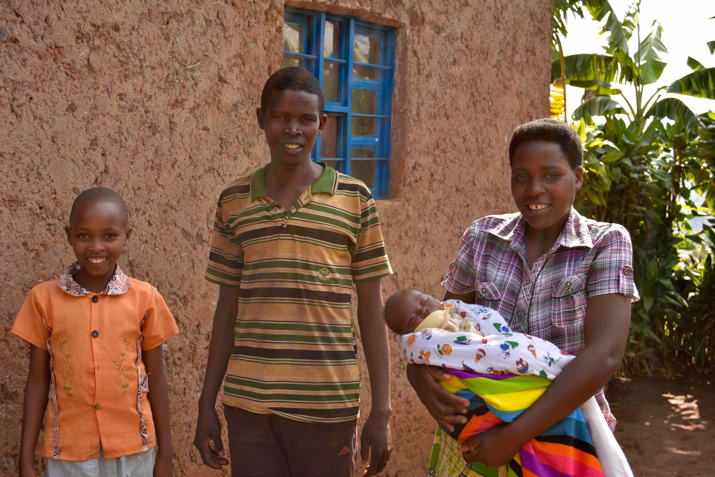 Claudine poses with her family outside their home in Bumbogo.