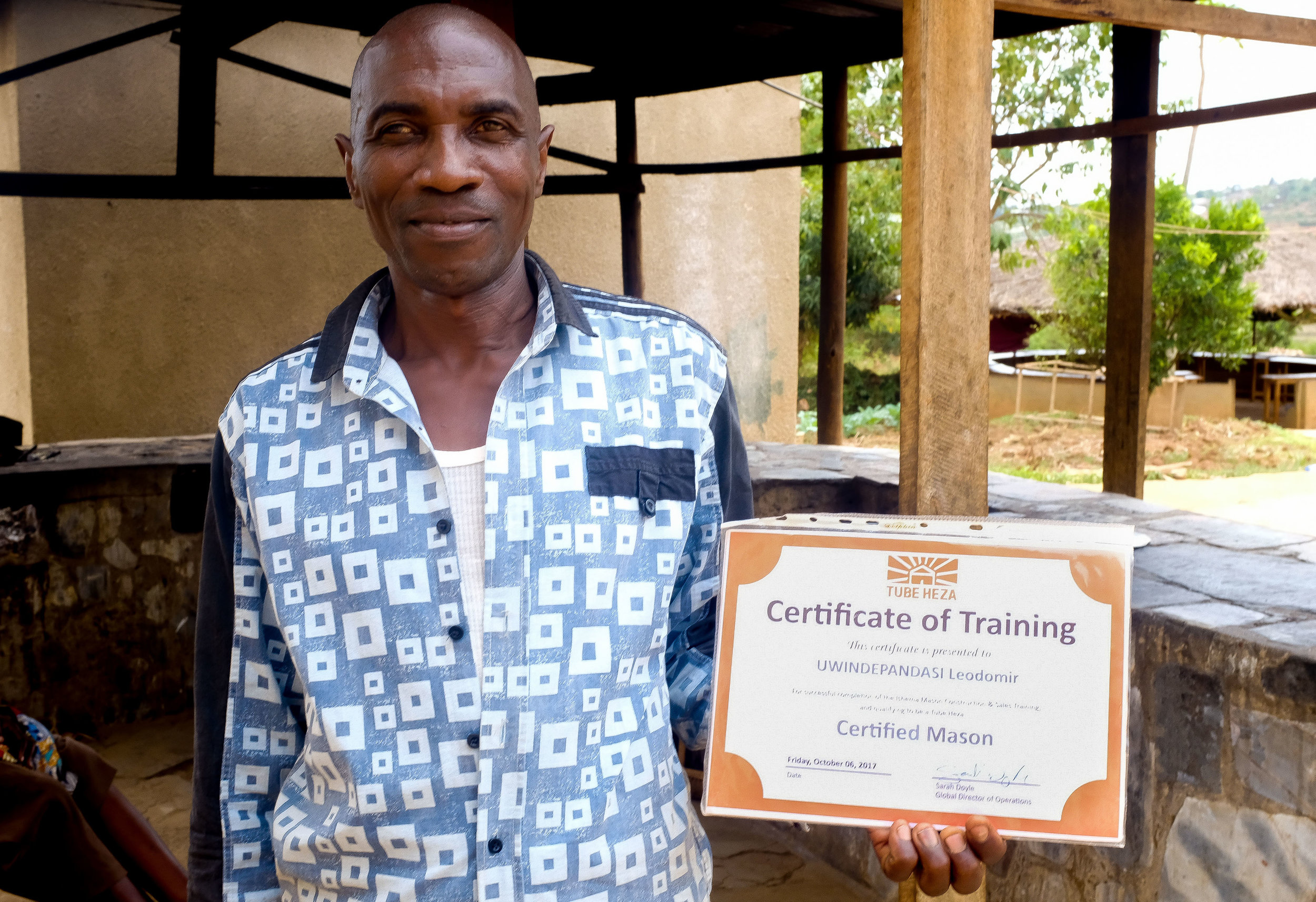 Rasta shows his    Earth Enable    certificate that confirms his certification for learning how to build the Earth Enable floor. He built an earthen floor for our farm Early Childhood Development program.