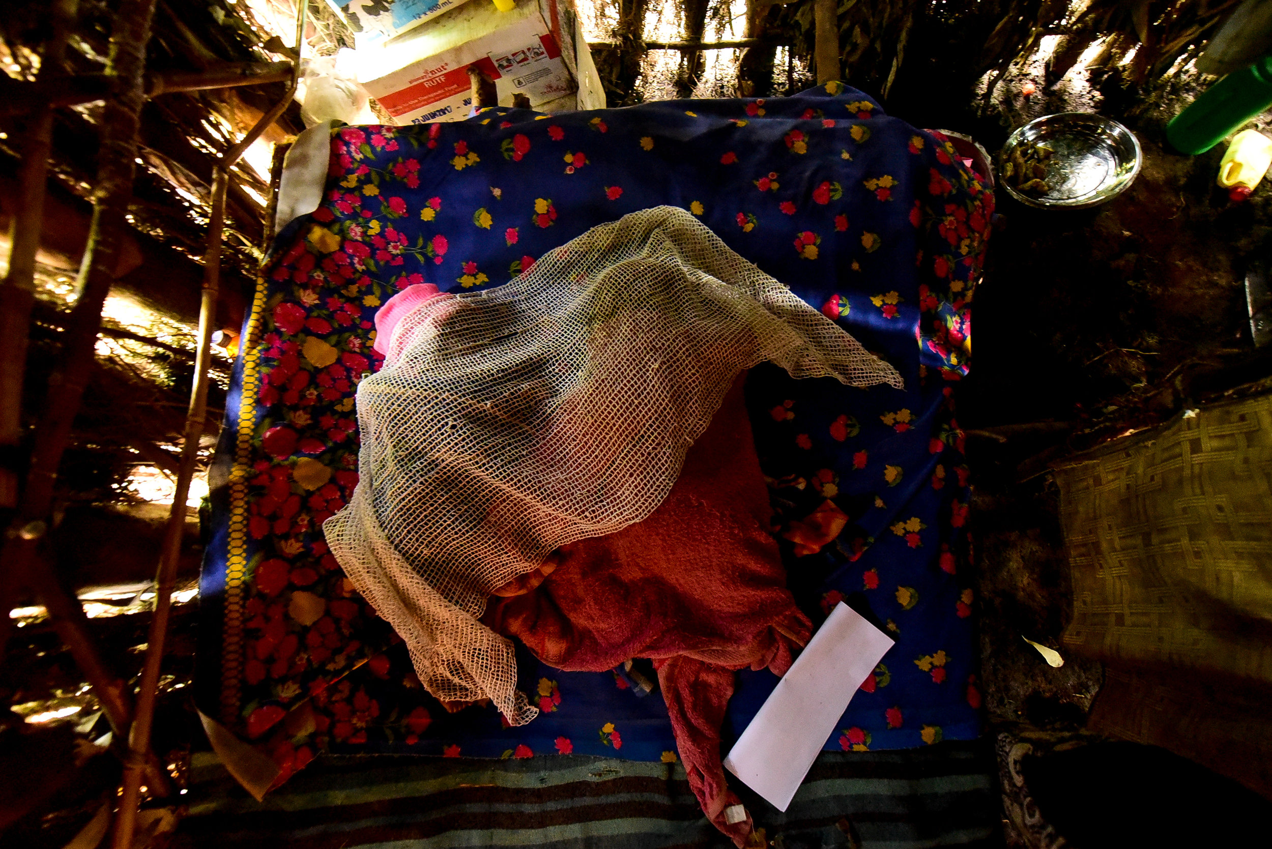 Uwiduhaye Divine and Muhawenimana Kevine sleep in the single bed their mother Nyirantugane Claudine and her husband own. The family of four lives in a single room shack made of banana leaves.