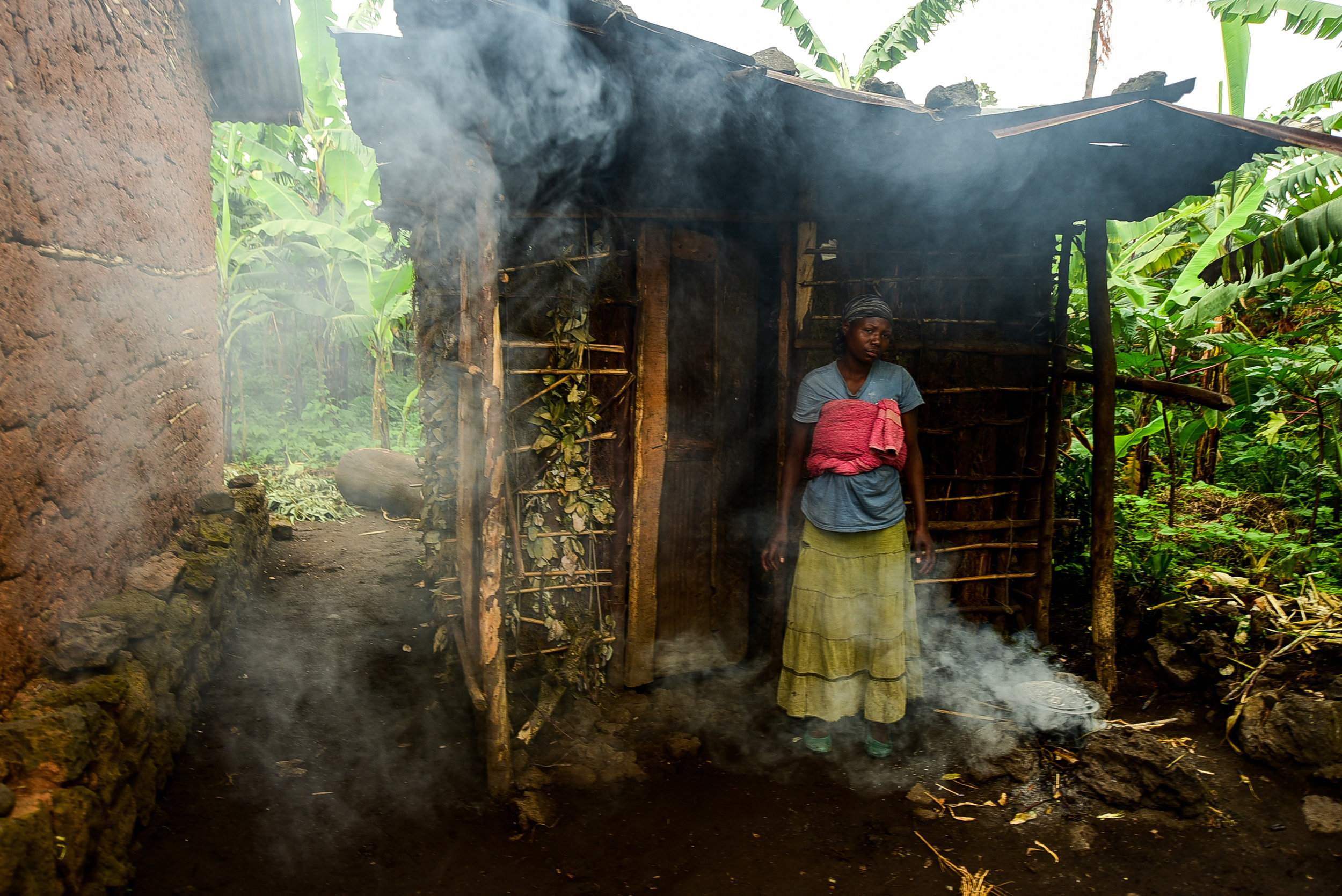 When Nyirantugane Claudine gave birth, she had to sell the iron slats she had saved up for as a roof for her new home to pay the hospital bill. Instead of living in the home of her in-laws (pictured left), she, her husband, and her daughters live in a small shack made with wood and banana leaves. Housing insecurity is a huge contributor to malnutrition. Uwiduhaye Divine and Muhawenimana Kevine are often sick from the rain that leaks through the porous roof, and visits to the health center are expensive because the twins are not registered for health insurance. Their medical bills are such that Claudine often cannot afford food.