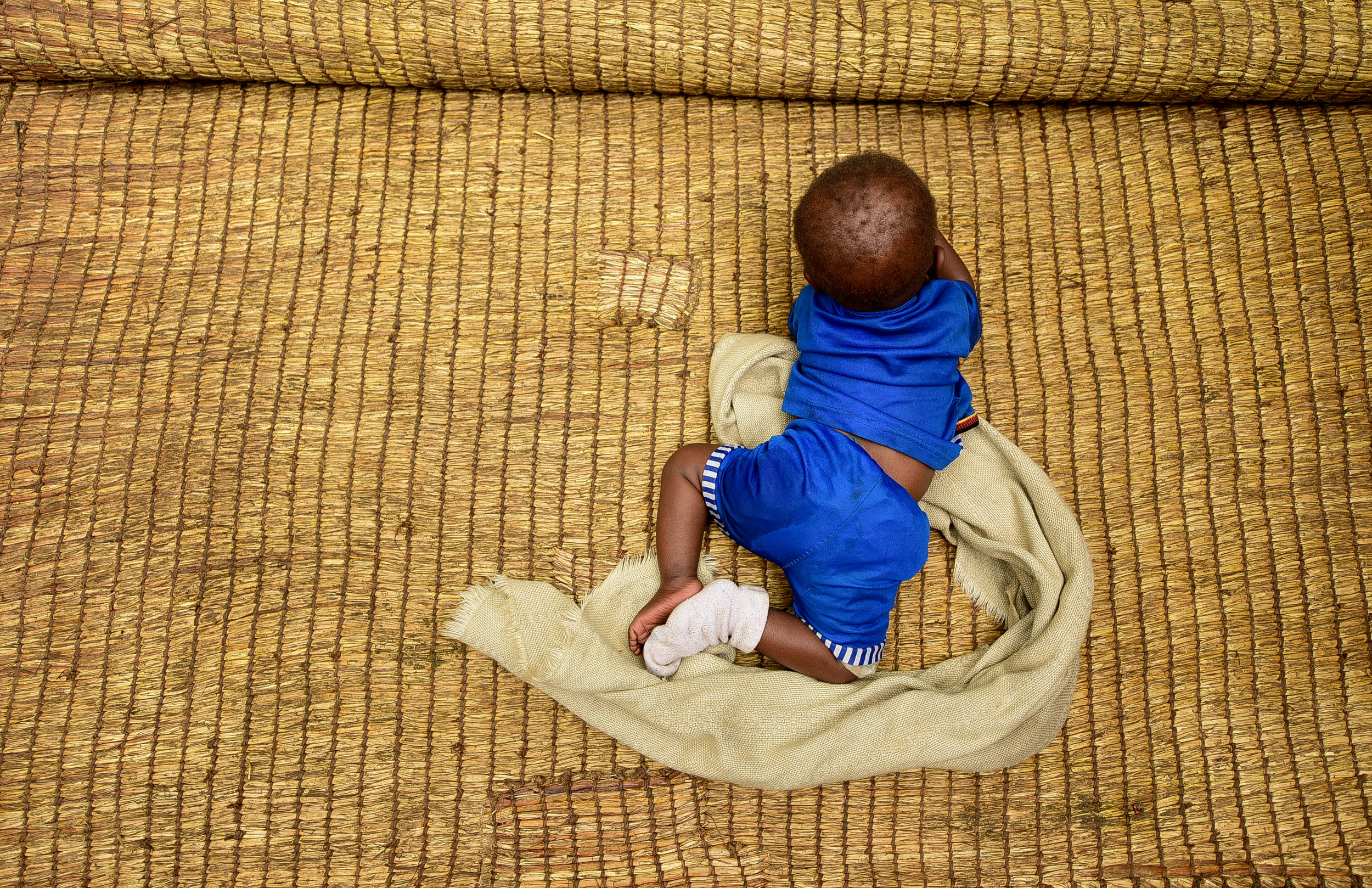 Uwiduhaye Divine waits for her lunchtime Sosoma, a fortified porridge blend of soy, sorghum, and maize meant as a nutritional supplement for children.