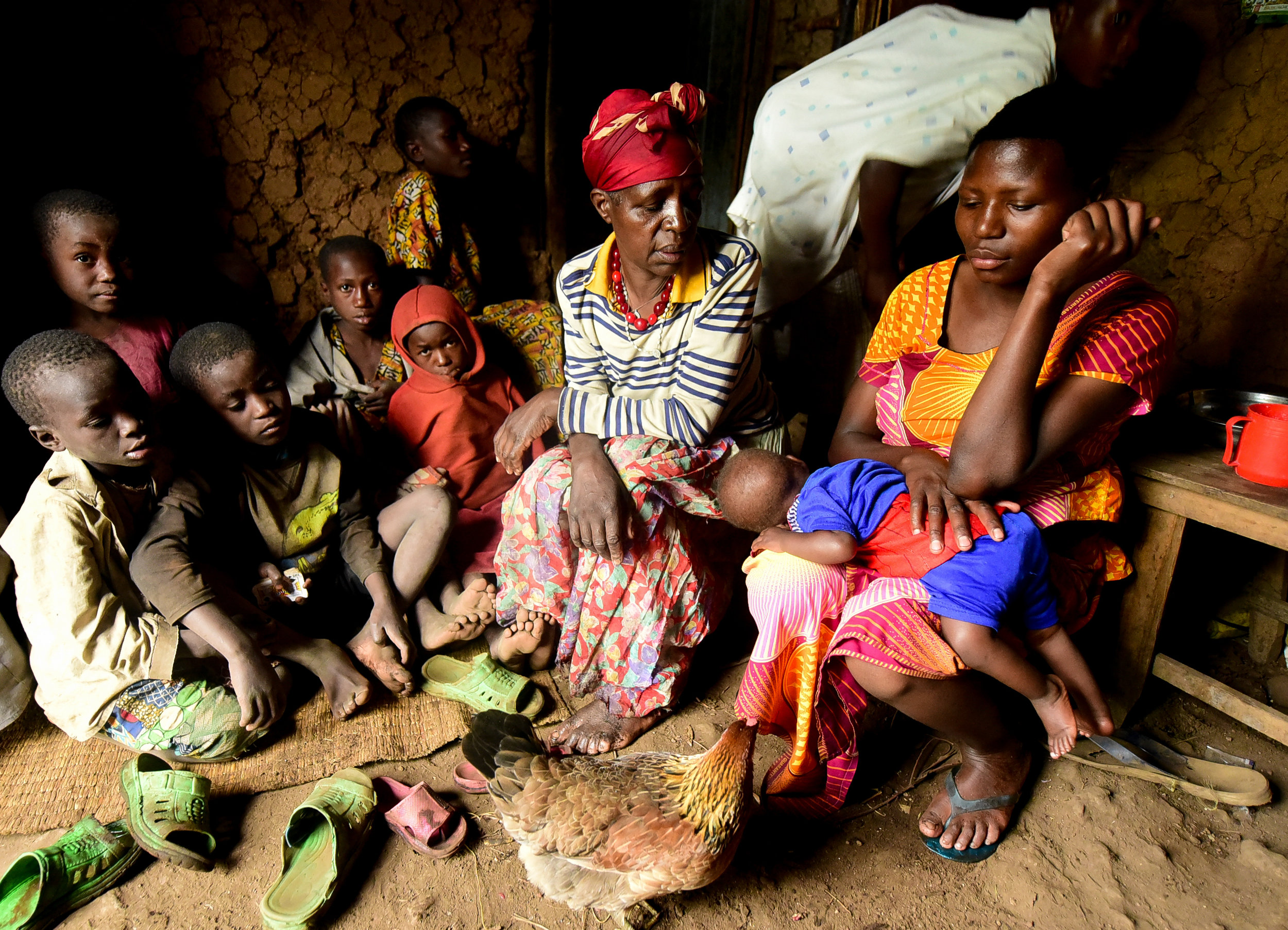 Nyirantugane Claudine sits with her mother-in-law, Mugurwinka Felronie, and several family members during a rainstorm in the house of her in-laws. Claudine and her husband live in a shack on the property of Felronie and her husband.