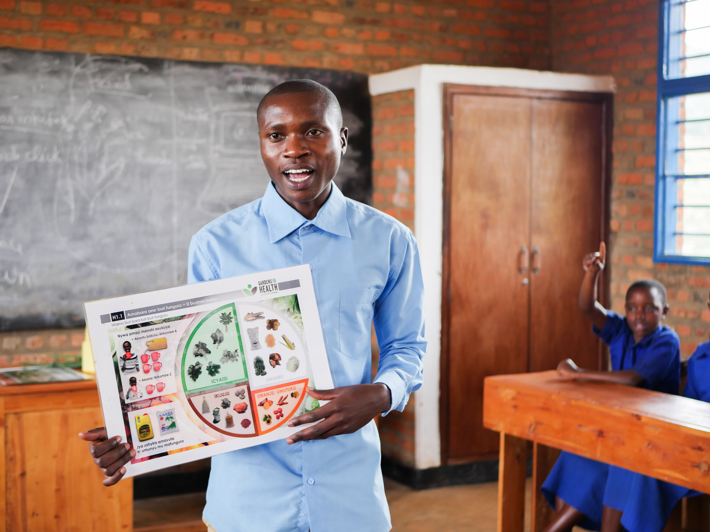 Placide, a teacher at Kabilizi Primary School, gives a lesson on the food groups that make up a balanced diet.