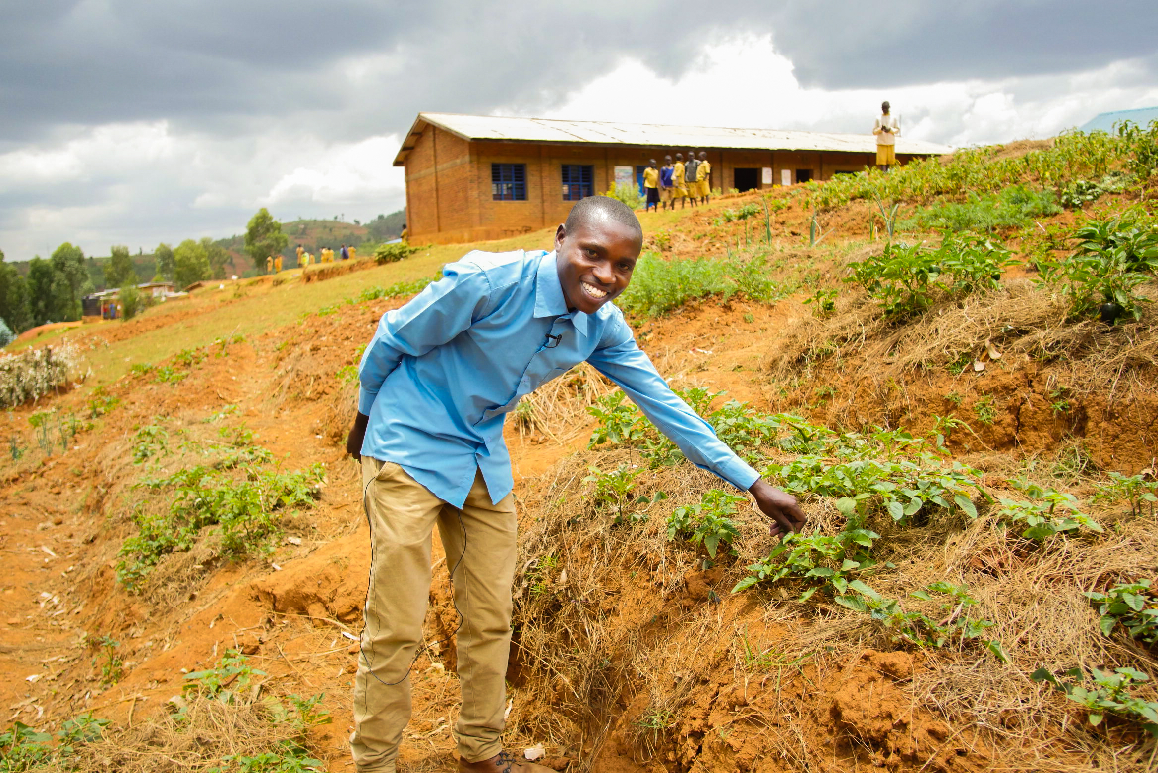 Placide proudly shows off his school's new vegetable garden, where fresh vegetables are starting to ripen.