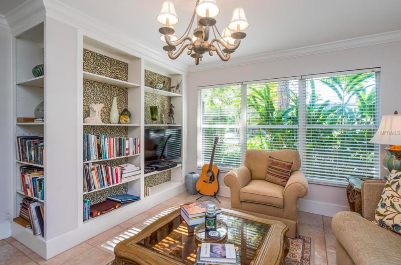 This bright living space also spotlights the verdant grounds and features clever built-ins that is just waiting to proudly display trinkets from travels, collector's editions, and your favorite pottery & art.