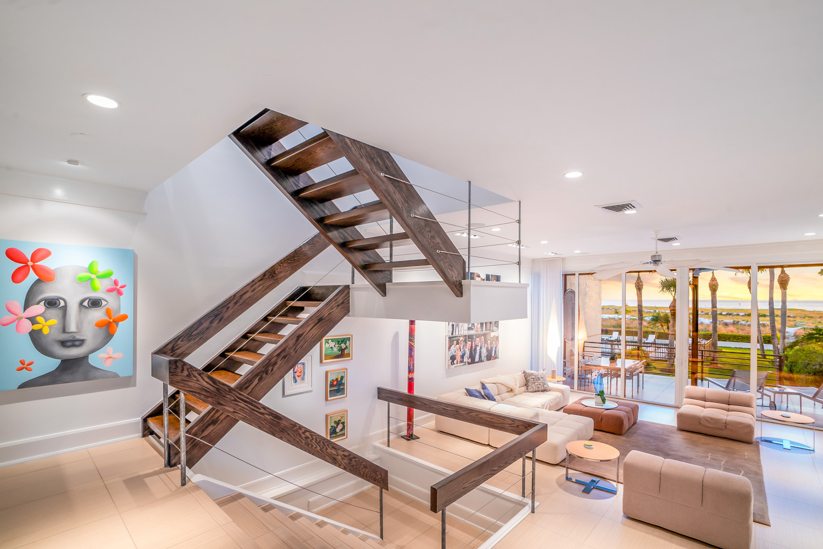 An amazing open floor plan allows the view to be enjoyed from all living spaces. Contemporary details like the wood-and-cable staircase keep the space interesting while allowing the eye to ultimately draw right to the sunset through the frame of the wide, full-height sliders.