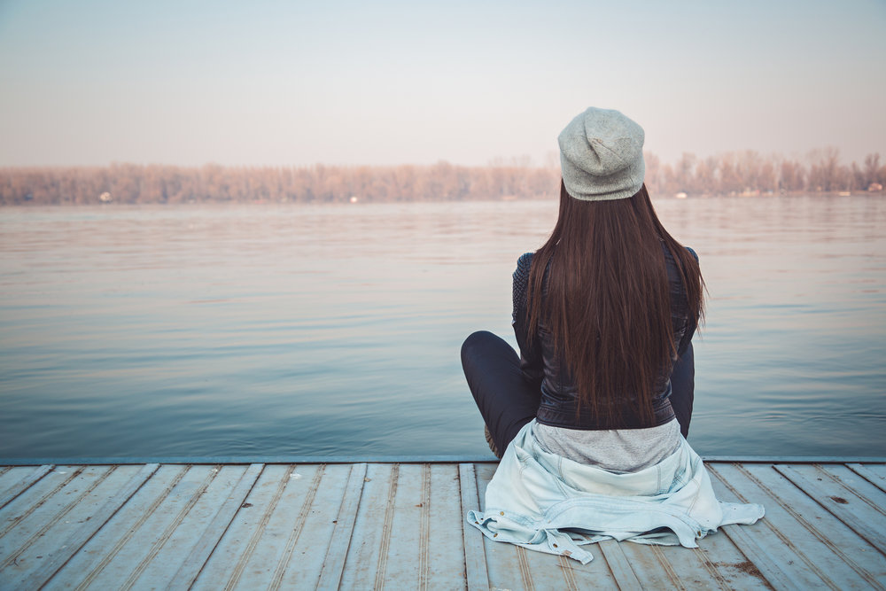 Girl+sitting+on+pier+and+lookingat+the+river.jpg