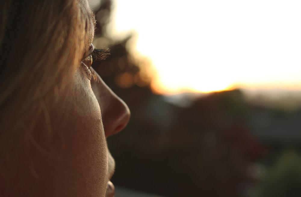 woman looking at sunset, thinking.jpeg