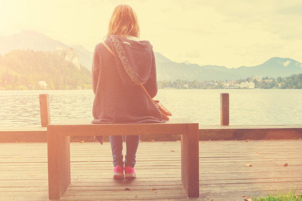 woman sitting alone on bench at lake.jpeg