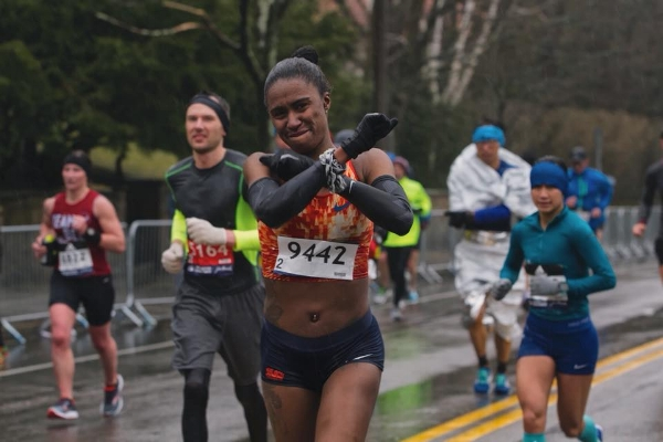 "Dannielle gives the ""Wakanda Forever"" salute as she braves icy rain at the 2018 Boston Marathon. Photo: Samuel Okpakoh Ayide"