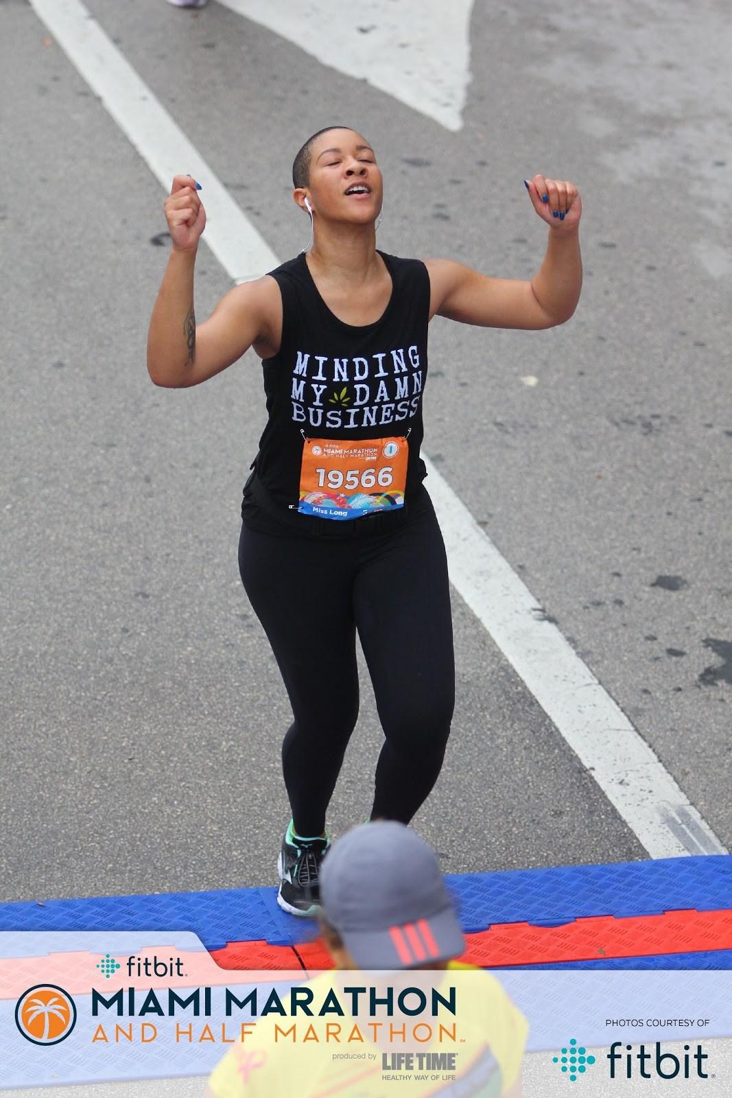 The author celebrates as she crosses the finish line of the 2019 Miami Half Marathon. Photo via TiYanna Long