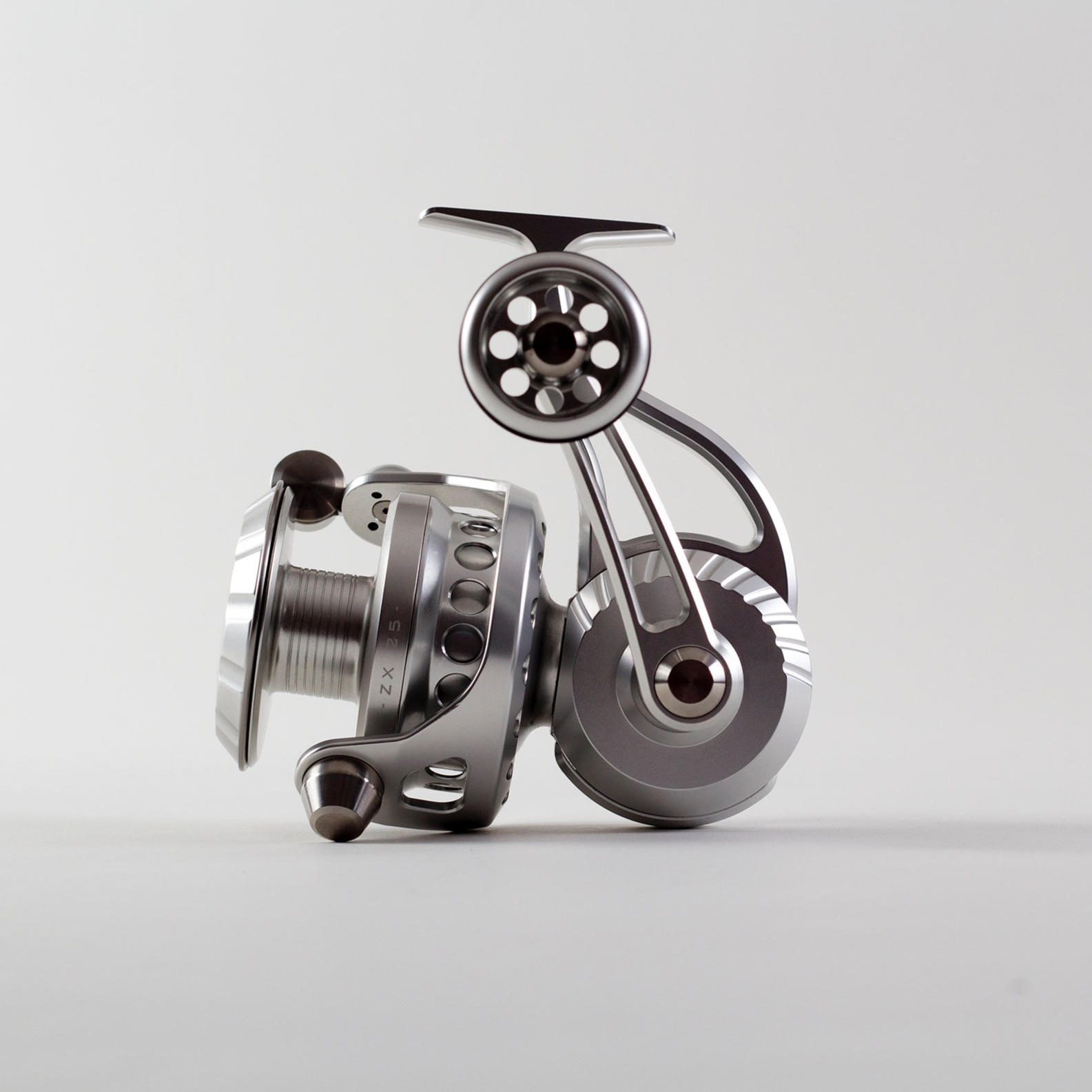 "ZeeBaaS ZX-25 - The ZX-25 is favored by most surfcasters using a 10.5'-12' rod. This model fishing reel provides plenty of line capacity for those throwing big plugs from shore, or dropping plenty of line off-shore and requiring the big, smooth drag performance. Like all of our reels, the ZX-25 is fully sealed and completely waterproof. We offer the ZX-25 in black, silver or a combination of black and silver which we refer to as our tuxedo edition. Custom colors and personal engraving are also available for an additional charges. Contact us for details.Our ZX-25 DeliversSpool Diameter: 2.5""Weight: 21.6 ozGear Ratio: 4.75:1Capacity: Mono: 400/15 - Braid: 450/30Retrieve: 35.5"" per turnMax Drag: 35lbsAble to be self-maintained or factory maintained.Starting at $979.00"