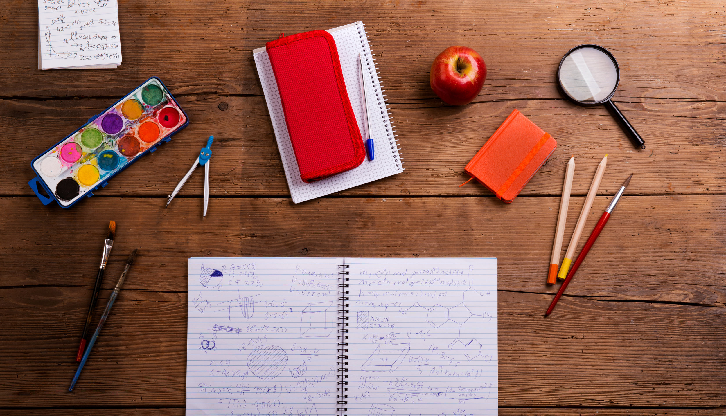 graphicstock-various-school-and-art-supplies-laid-on-desk-flat-lay-notebook-with-math-symbols-and-formulas-studio-shot-on-wooden-background_H_FV9MrGW.jpg