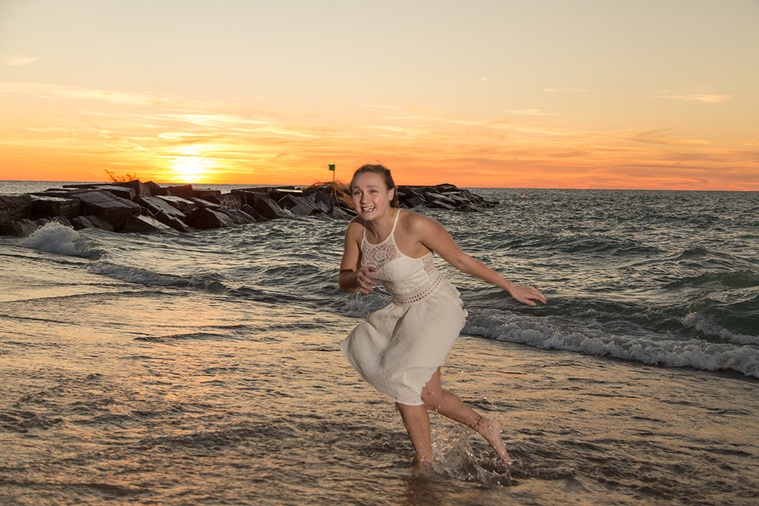 High school senior Veronica having fun in the water during her sunset senior photo session in New Buffalo. She is at home in the water - swimming for her high school swim team.