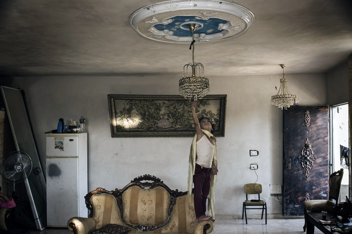 """The Khalifa family from the Occupied West Bank village of Walaja nervously awaits demolition orders from the Israeli government. The extended family of 17 have the original land deed and their great grandparents are buried just outside. One of the children reaches for a """"Sistine Chapel"""" light fixture designed by her father of clouds and blue sky. The Un/Holy Land is an interactive documentary, taking viewers on a deep and multi-layered dive into the sacred and profane landscapes of Israel-Palestine. Our web-doc is a multi-sensory digital platform that re-engages myth and dogma, moving the viewer through rigid and contested boundaries customarily drawn around faith, secularity, religion, and politics.  We engage and challenge viewers in playful new way, giving them a uniquely complex and dynamic path for learning and unlearning the lay of the Un/Holy Land."""