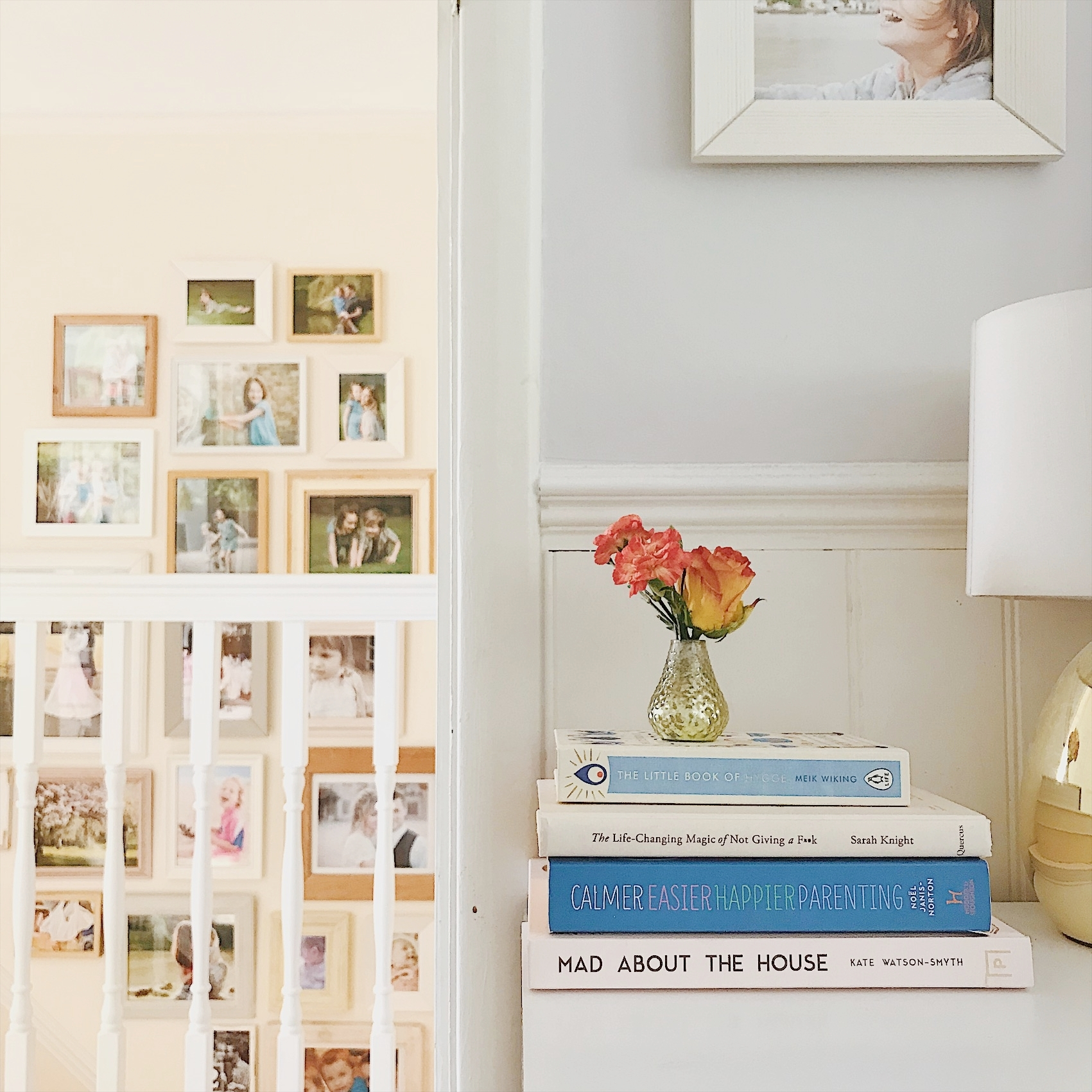 Gallery wall of family portraits above the stairs in pale wood, white and pastel coloured frames