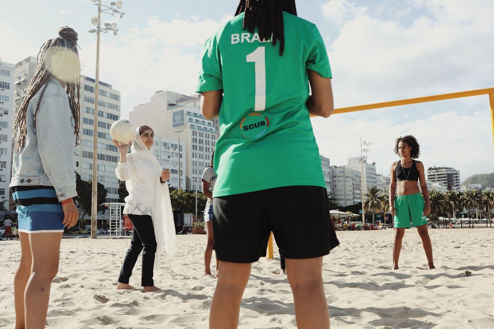 Malala desfruta de um jogo com a equipe vencedora do Street Child United Brazilian Girls. (Cortesia de Luisa Dorr / Malala Fund)