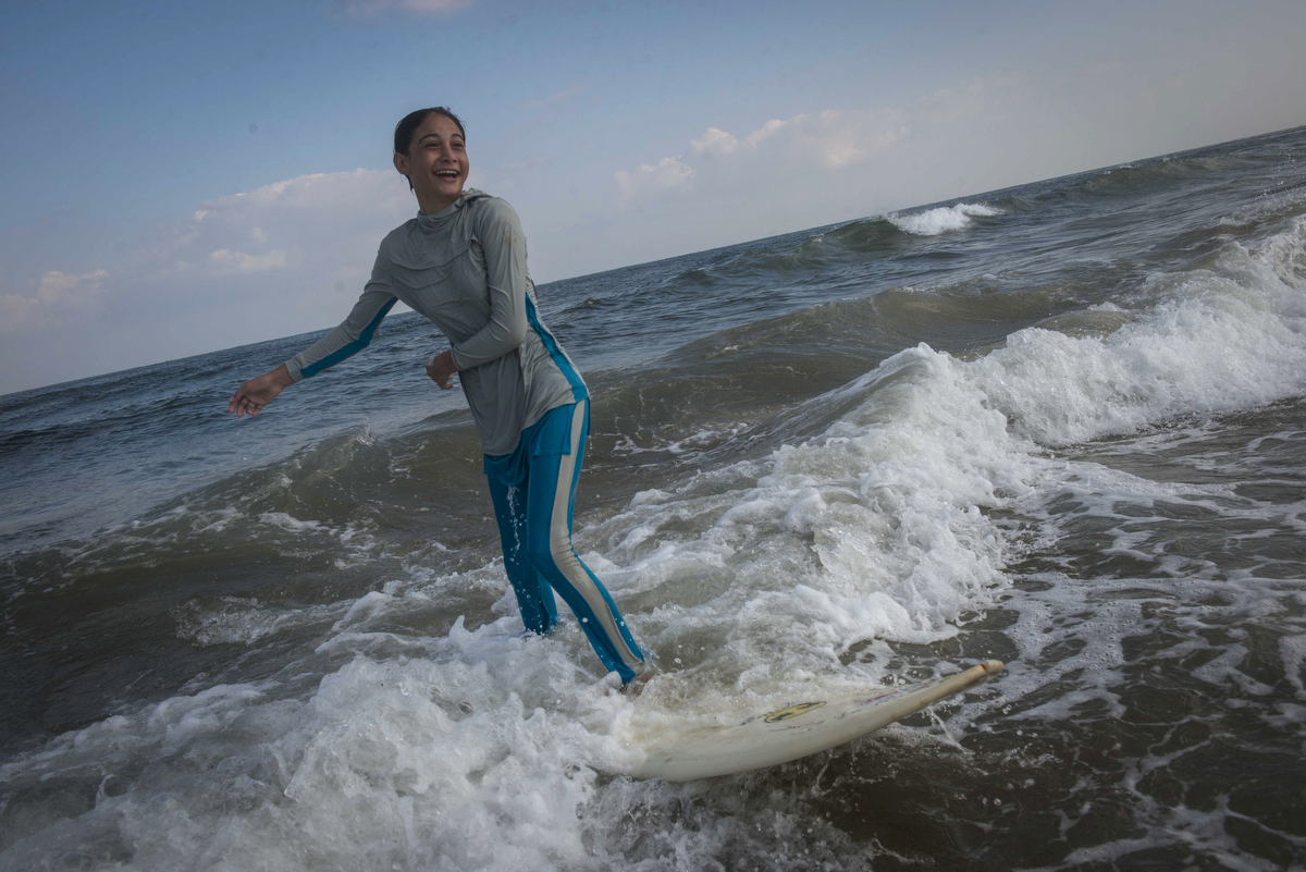 For many Gazans, the sea is the only place they can be without being reminded of their isolation. 14-year-old surfer Sabah Abu Ghanem and her sister surf early in the morning outside of Gaza City. The sisters place first in many competitions inside the strip, but have never left the Gaza Strip to compete. (Courtesy of Monique Jacques)