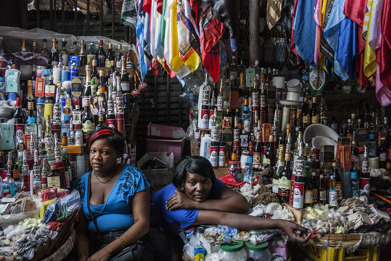 In a street market in Cap-Haïtien Maryse (at right) and her friend Martine sell religious products used for Vodou rituals and ceremonies. (Courtesy of Philomène Joseph / FotoKonbit)