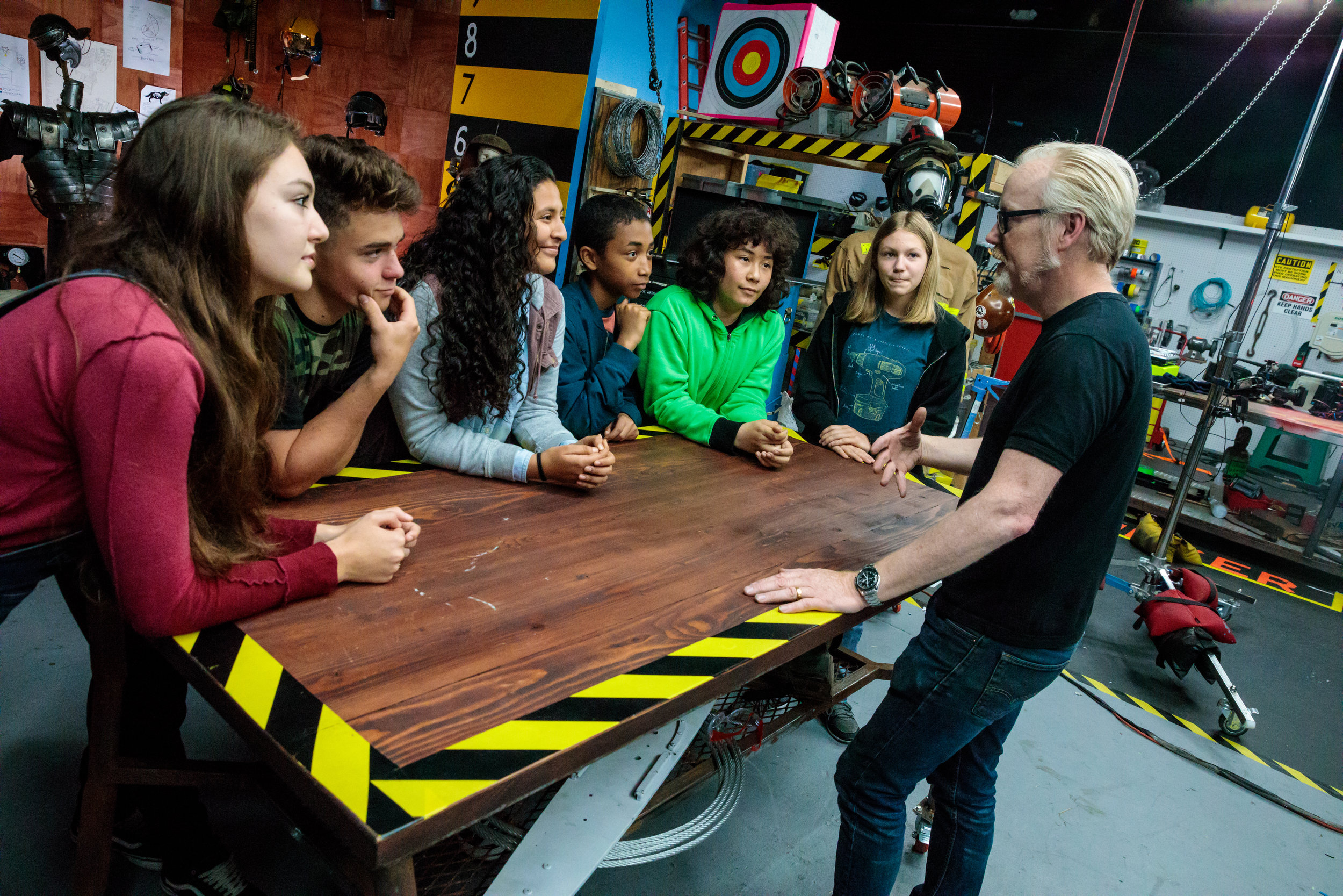 """Rachel Pizzolato (far left), Valerie Castillo (center) and Allie Weber (second from the right) on set with host Adam Savage on the """"Mythbusters, Jr."""" set. (Courtesy of Science Channel)"""