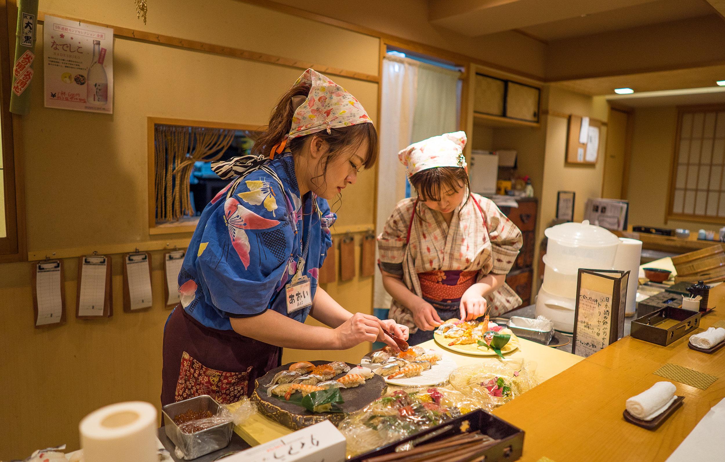 Yuki and a fellow sushi chef plate dishes to serve at Nadeshiko Sushi. (Courtesy of Amarachi Nwosu / Malala Fund)