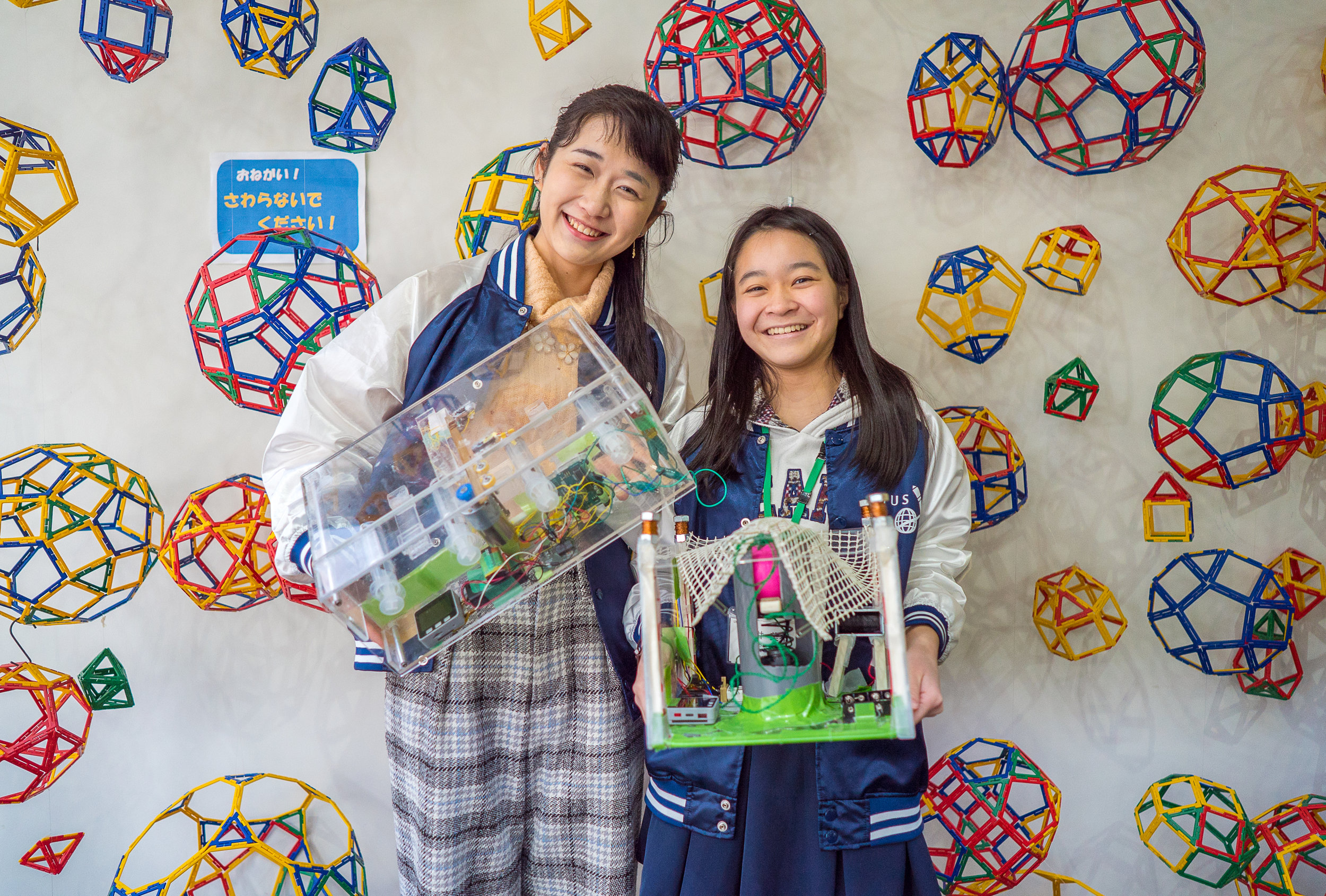 Emiko (left) and Miki (right) pose with the devices they built as part of the Space Education programme at the Tokyo University of Science. (Courtesy of Amarachi Nwosu / Malala Fund)