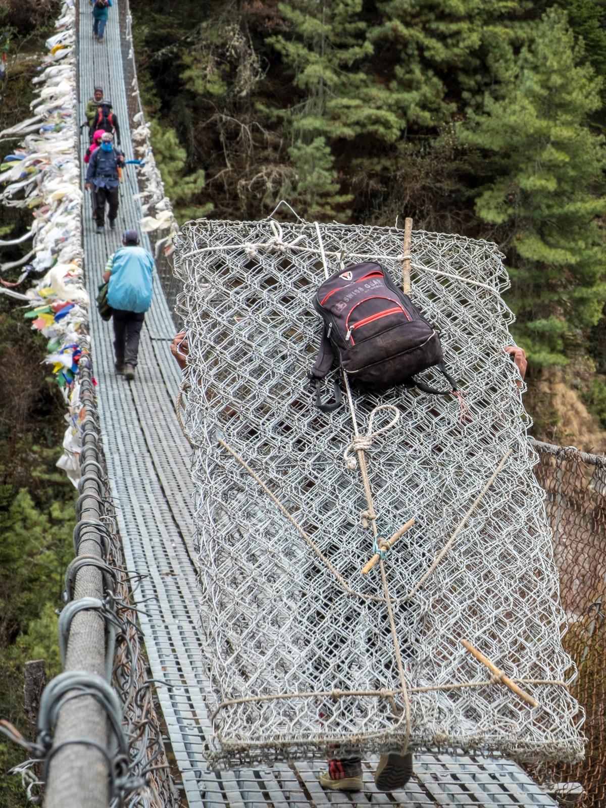 Porter crossing a suspension bridge, Nepal.