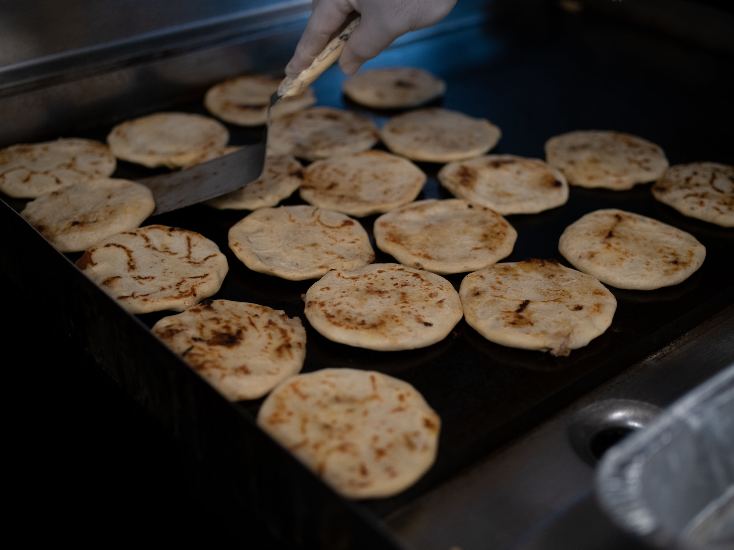 Pupusas on the griddle at D'Maize. Image courtesy    DoorDash   .
