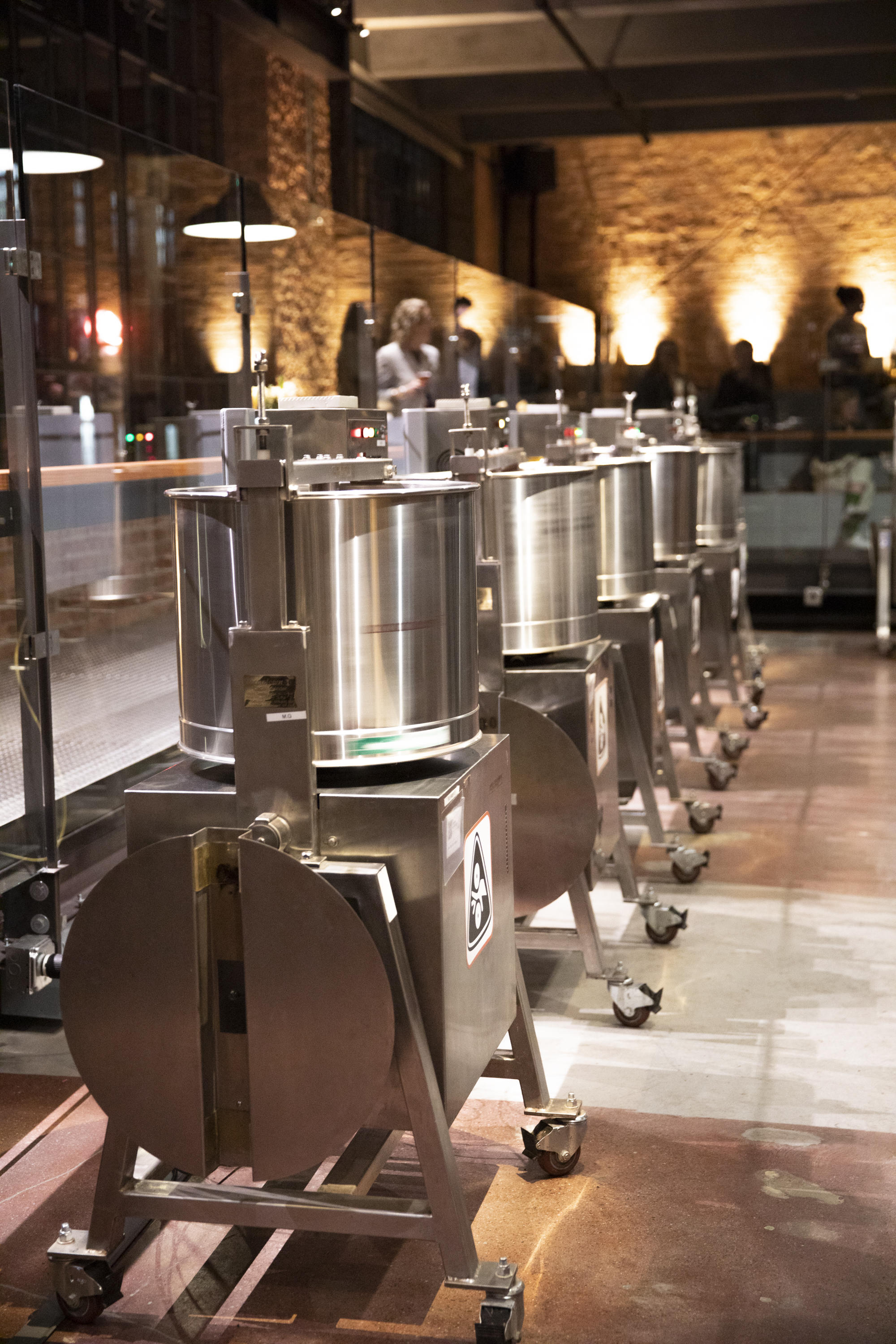 On display: A row of machines designed to grind down cacao nibs and sugar so that the ingredients fully integrate and form a silky, chocolate liquid. Photo:  Anne Fishbein