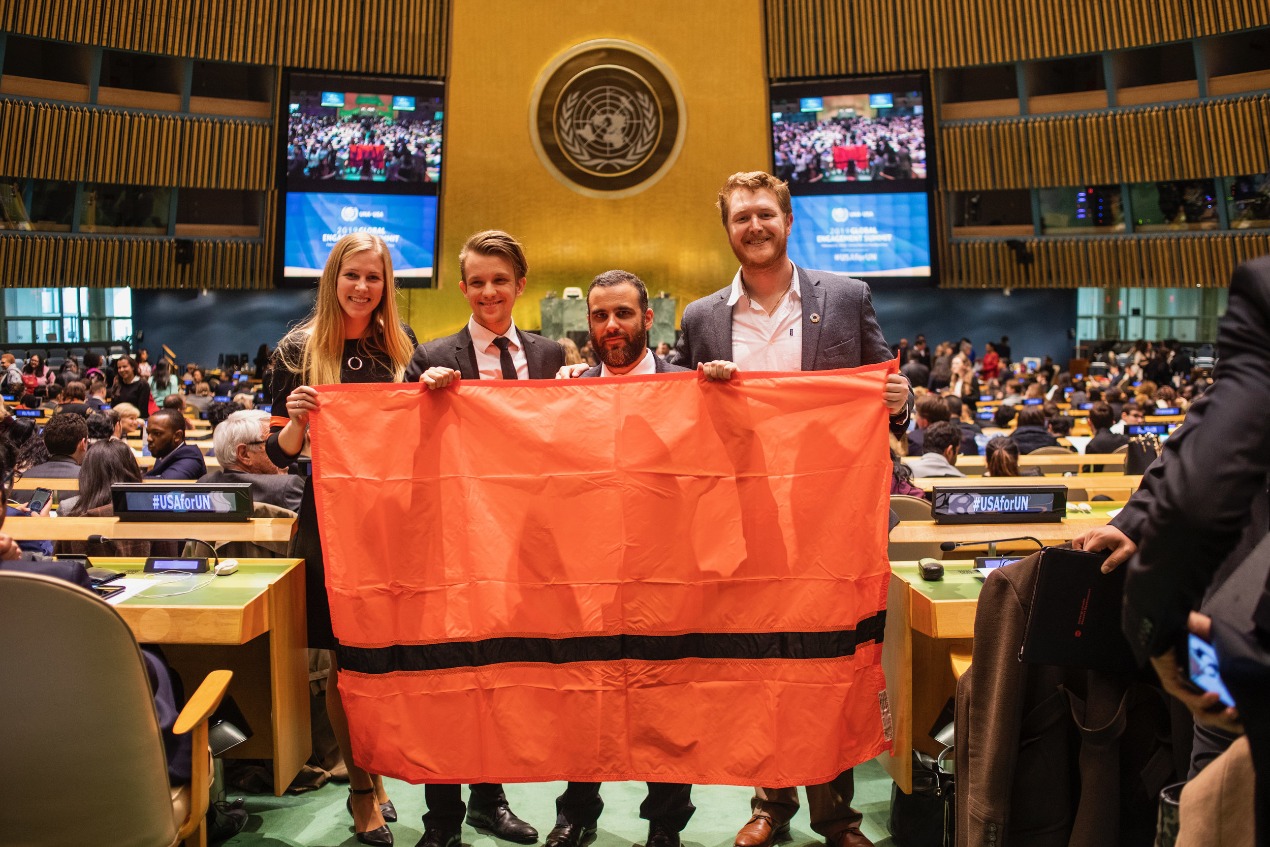 The IOR delegation can be seen holding a gift, the Refugee flag, from the Refugee Nation at the New York HQ, 2019 United Nations Global Engagement Summit. Pictured from left to right: Caroline Kurdej, Sebastian Agignoae, Juan Lazo Jr., Christopher Dowell.