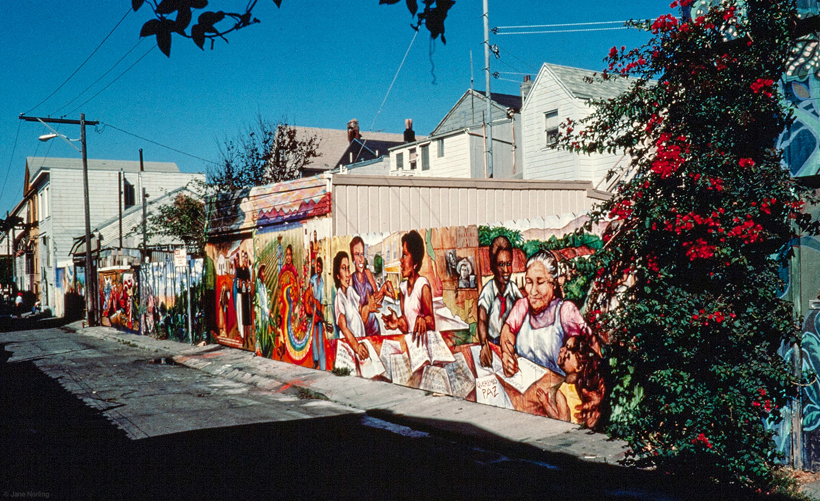 "Y Enseñarles a Leer/And Teach Them to Read , PLACA murals project, Balmy Alley, San Francisco, 1984. ""I used to feel I was apart from the world. Now I know I'm a part OF the world,"" literacy student comment, lower left."