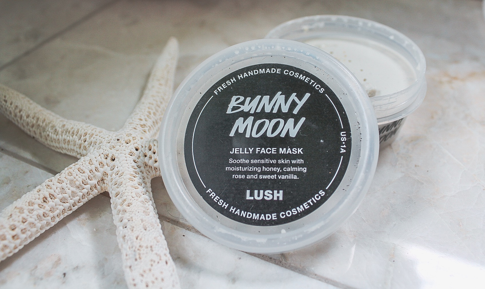 Photo description: A pot of Lush's cream colored Bunny Moon jelly face mask is sitting on a marble counter open with the top leaning on it. There is a white starfish next to it.