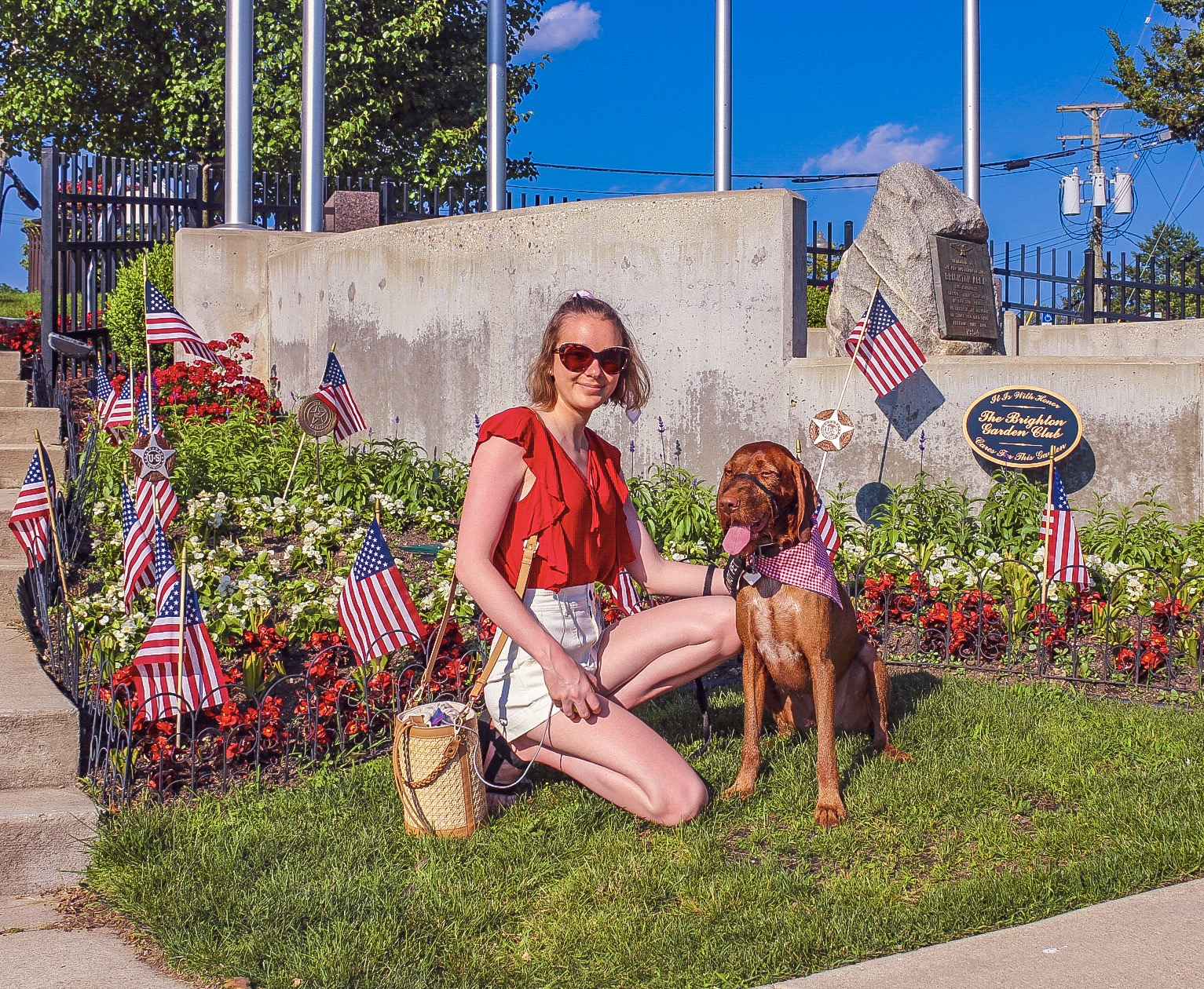 Image Description: Cienna and Piper(a red wirehaired vizsla) sit on grass in front of a garden full of red and white flowers with American flags. There is a rock veteran memorial behind them. Cienna is smiling wearing sunglasses, a red ruffle shirt, cream shorts, with her pacemaker wire running out from between her shirt and shorts to a woven basket bag. Piper is wearing a red gingham bandana and squinting at the camera with his tongue out.