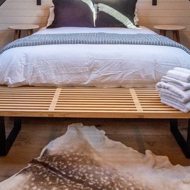 The bedroom of this Healthy Hut has been styled with light simple decor to allow the textures of the room to take president.  #blackhutdesigns #blackhutstays #bedroomdecor #compacthousing #adnz #timberpaneling #blackandwhite #fionamacpherson