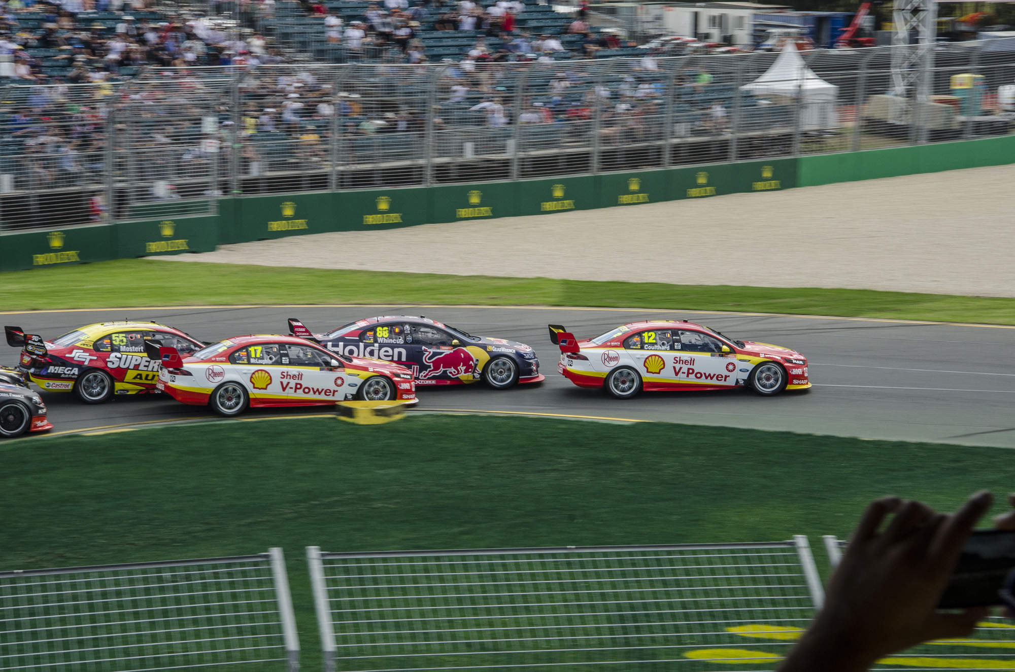 Redbull racing Commodore driven by Jamie Whincup up against the Shell V-power Falcons with Fabian Coulthard in the lead at turn 1 of the 2017 Melbourne F1GP