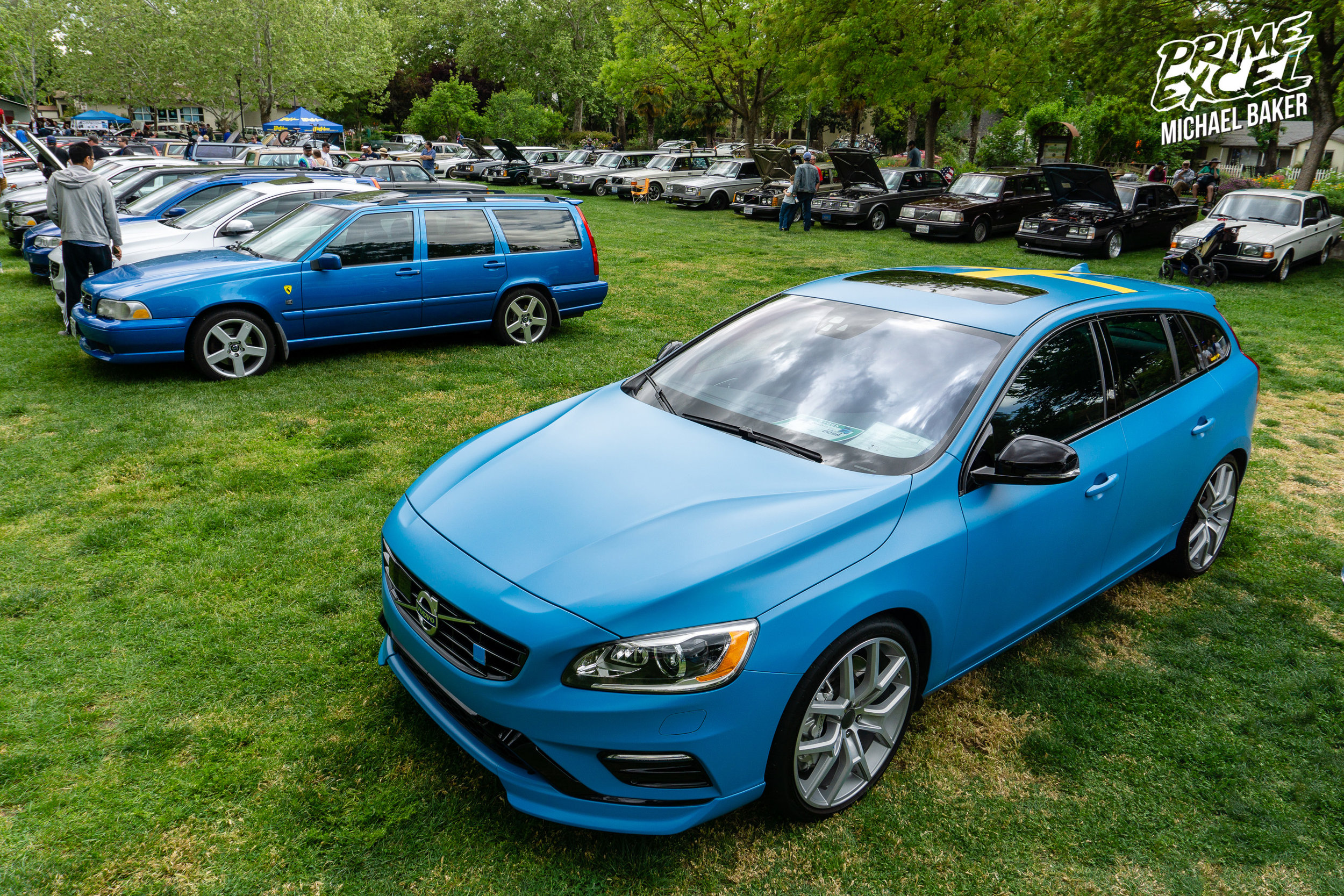 """A Volvo V60 Polestar, in Polestar Blue, with a clear matte vinyl wrap on top. As you can see, the park was divided up by model with a row of """"R"""" cars followed by a row of 240s."""