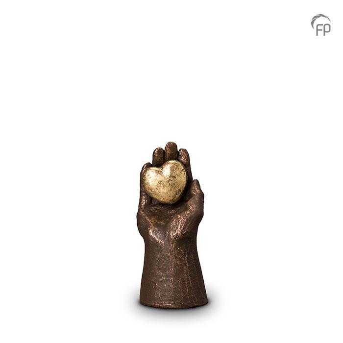 UGK 004 A  Keramische urn brons Hand met hart  Elke Geert Kunen urn is uniek en wordt op bestelling gemaakt. Daarom zit er op deze producten een levertijd van 3 à 4 weken.  UGK 004 A € 99,00 / 0.10 L / H 15 CM