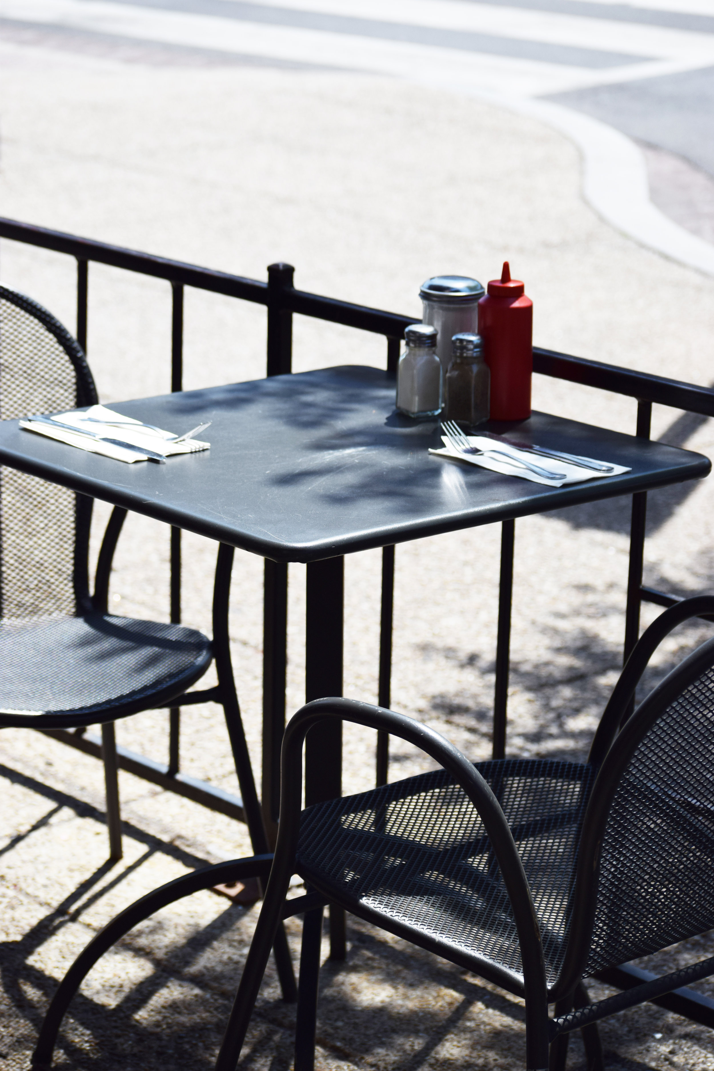 An empty table on the patio with cutlery and sauces