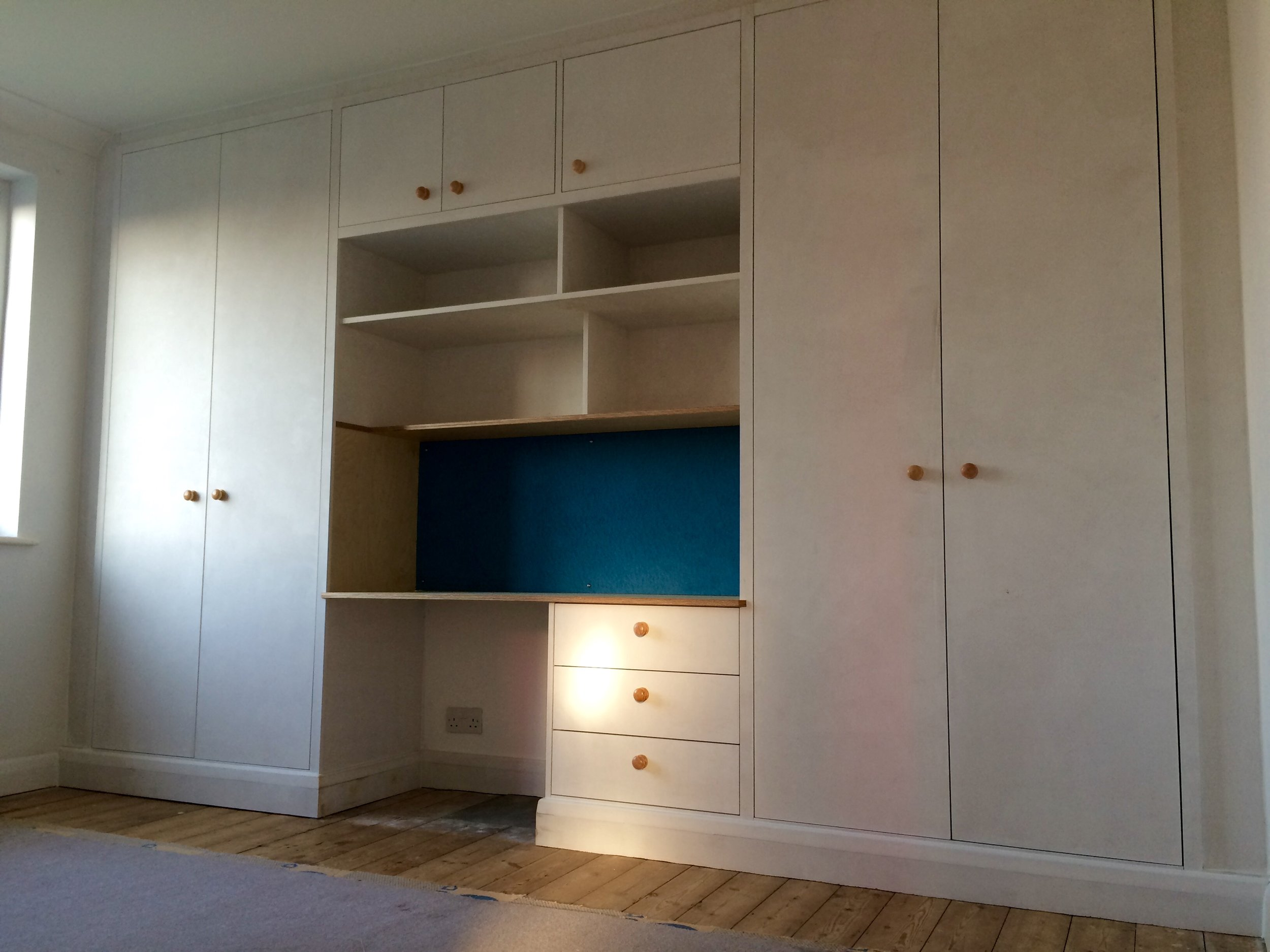 Functional - These wardrobes have melamine faced interiors, with primed doors and trim for the client to decorate. The desk area in the centre is made from prefinished birch plywood and a blue pin board adorns the rear.