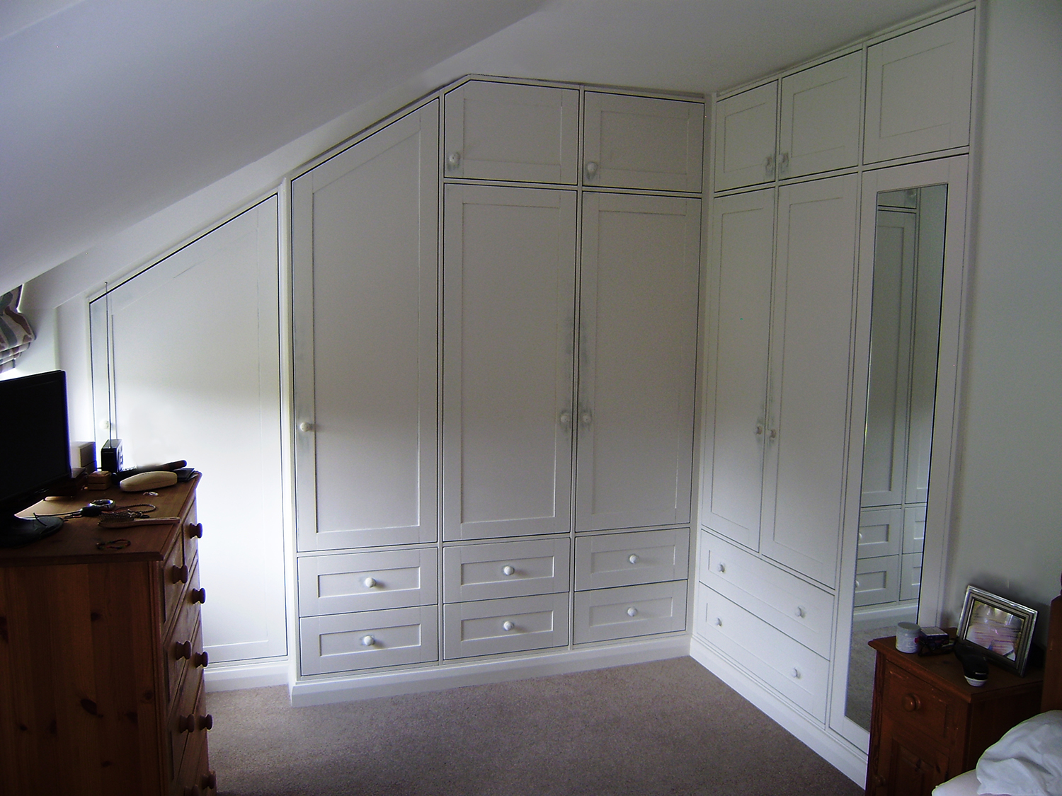- These fitted wardrobes have been painted in an off white colour with a darker undercoat beneath. The top layer has been gently sanded through to give a slightly worn appearance around the handles.