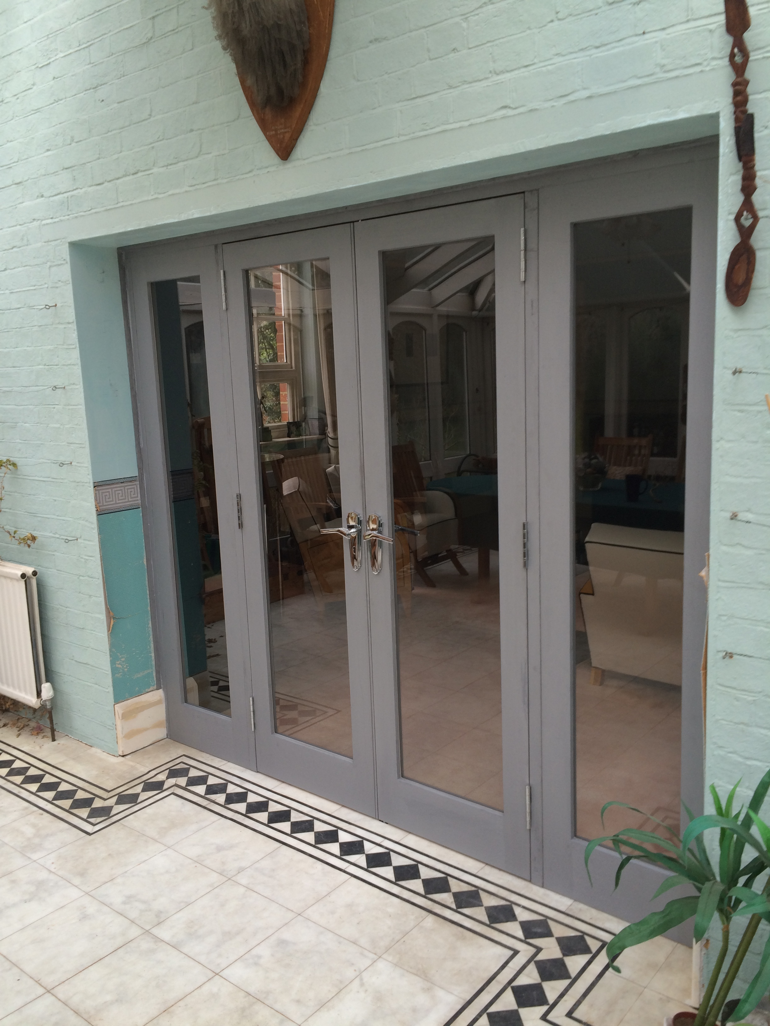 - These interior french doors separate the living room from a conservatory. The exterior (seen) is simple in form, whilst the interior has art deco detailing which complements the style of the room.