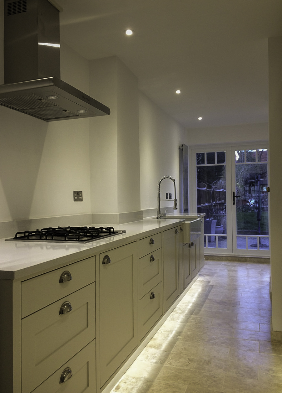 """Paint and stone. - """"We approached Ben about designing and building a bespoke kitchen when we were given extortionate quotes by kitchen designers who use 'off the shelf' carcasses. The shape of our kitchen meant there were lots of modification needed which inflated the price. As a furniture maker, Ben explained that he could make the cabinets to the kitchen's measurements thereby reducing the cost of labour and keeping the kitchen under budget but still having the high quality look we wanted. The design process was easy. We told Ben we wanted a shaker style kitchen with half-moon handles and Ben suggested having no wall units where there were previously. This allowed more light to come in from the new patio doors and not block the line of sight into the garden. After that we just left Ben alone in the old kitchen for a few hours whilst he measured every nook and cranny! Ben had some great ideas about where to move the appliances, what type of shelving to use and it was his idea to have the quartz worktop to give it the classy finish.We are thrilled with the outcome of the kitchen! The overall look of the kitchen is just what we wanted, and added extras like the under plinth lighting and curved cupboard at the end of the worktop add such a touch of sophistication that we couldn't possibly have had with an off-the-shelf kitchen. Ben is so easy to work with too, with comprehensive plans for all the other trades to work from, instructions left at every stage and multiple site visits. The attention to detail is what sets Ben apart from other craftsmen because he's so meticulous about not only getting the design just right, but making it look perfect too. Thanks Ben for the whole, painless process.""""Lilian, Beckenham, Kent"""
