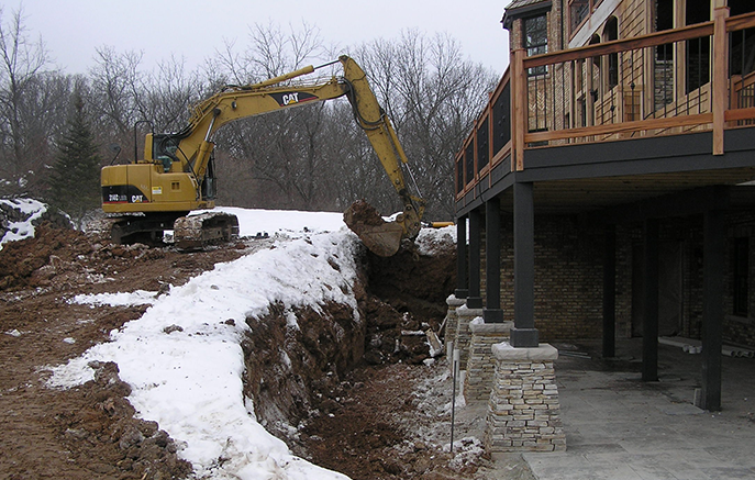 Excavation begins for a large outcropping wall with a stairway and a pondless waterfall.